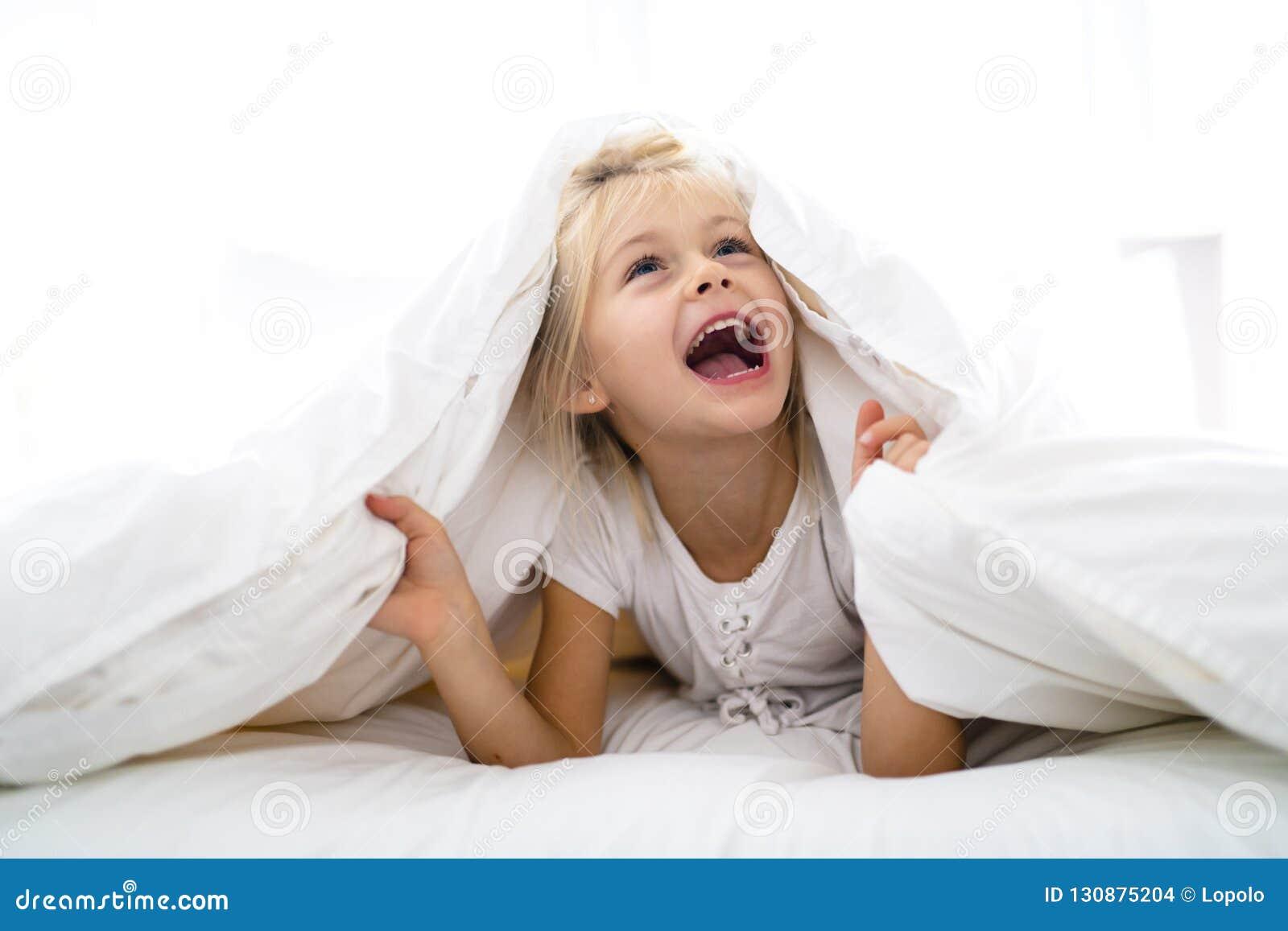 Una niña alegre en la cama que se divierte