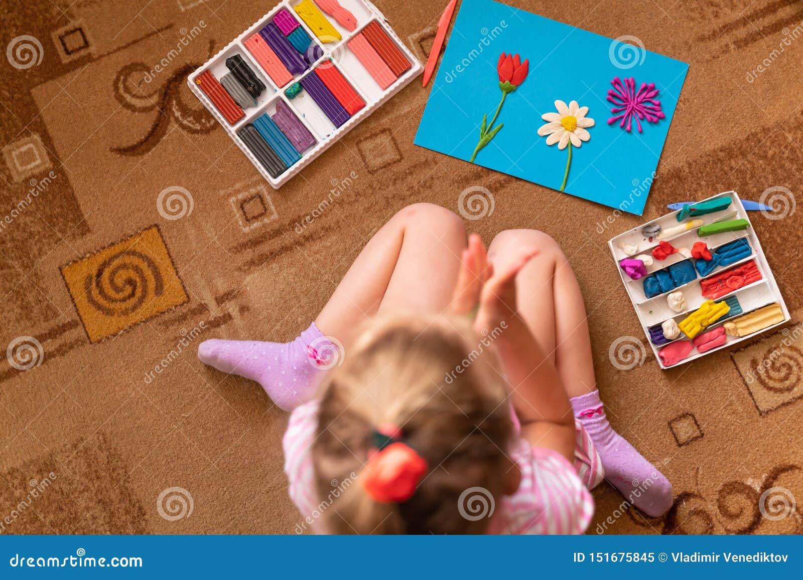 Una niña juega y esculpe de la arcilla modelado del plasticine y el desarrollo de las habilidades de motor finas