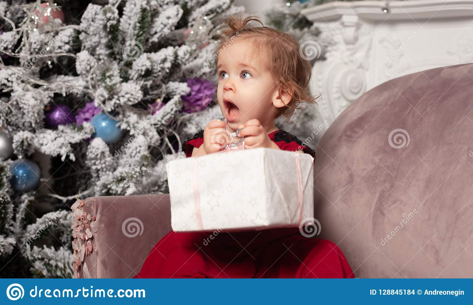 Una niña linda hermosa vestida en un vestido rojo de la tarde elegante se sienta en el sofá y abre un regalo del ` s del Año Nuev
