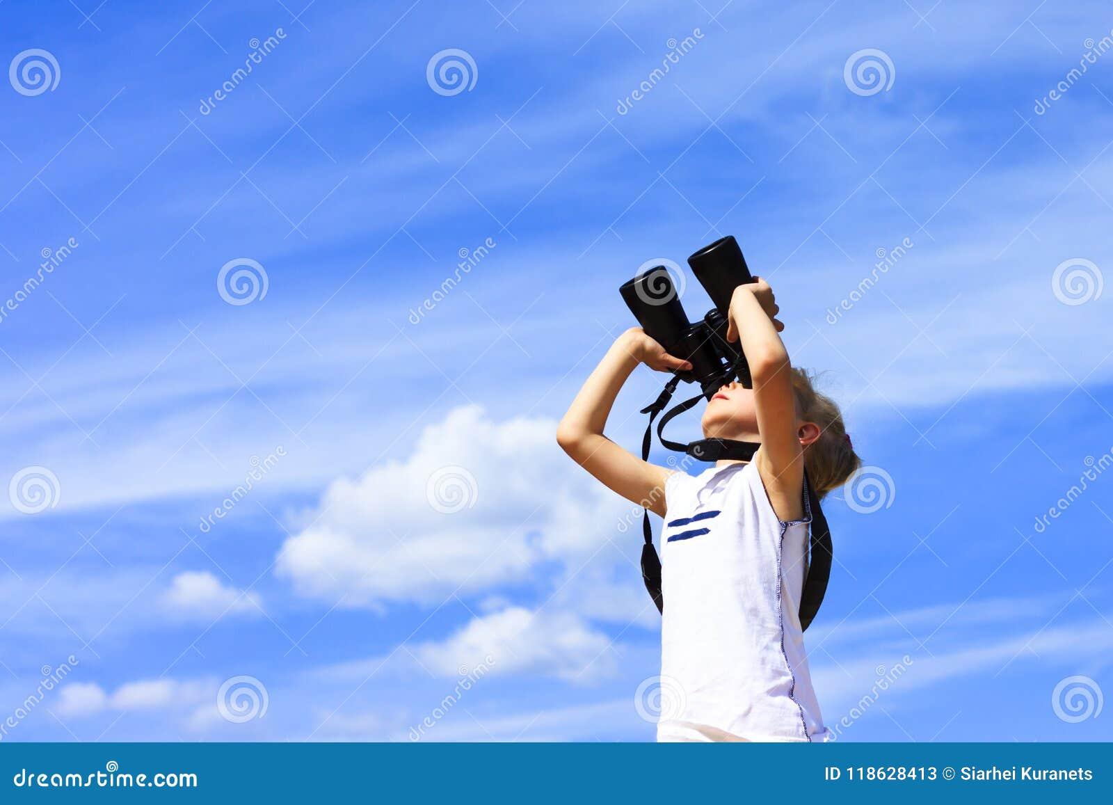 Una niña mira a través de los prismáticos Fondo del cielo azul Esperar un viaje a un país distante