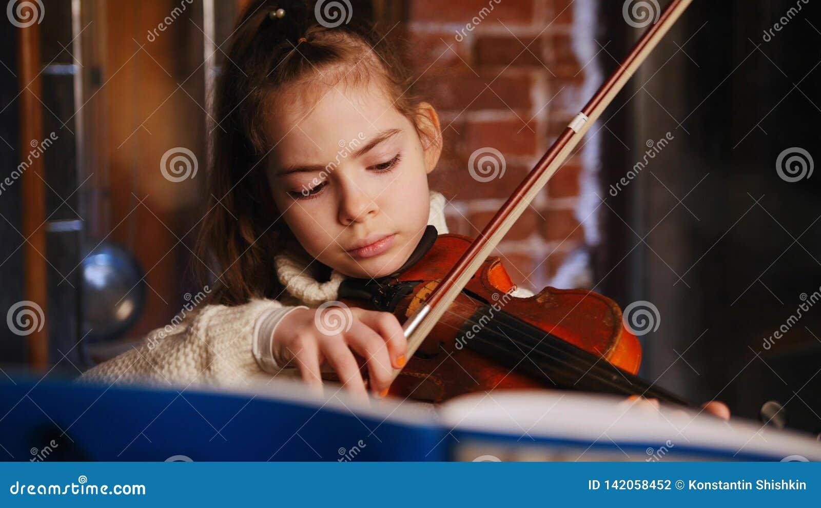 Una niña que aprende una composición por las notas Tocar el violín