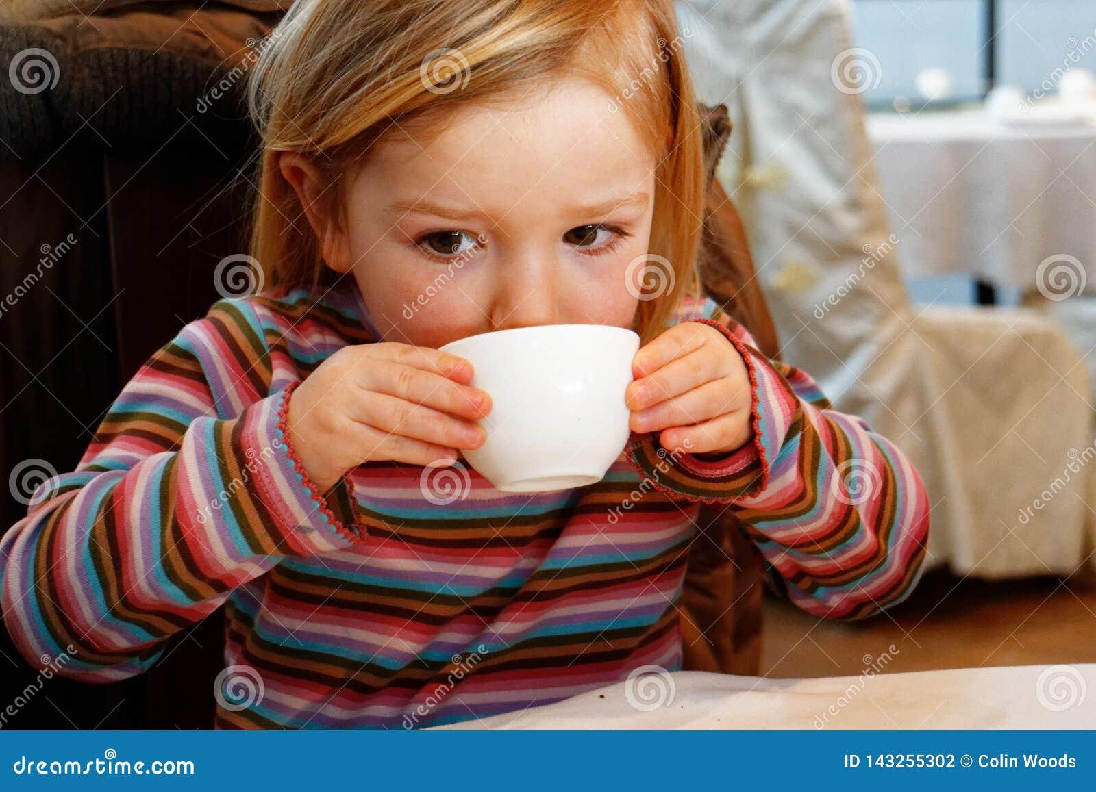 Una niña que bebe de una taza de té