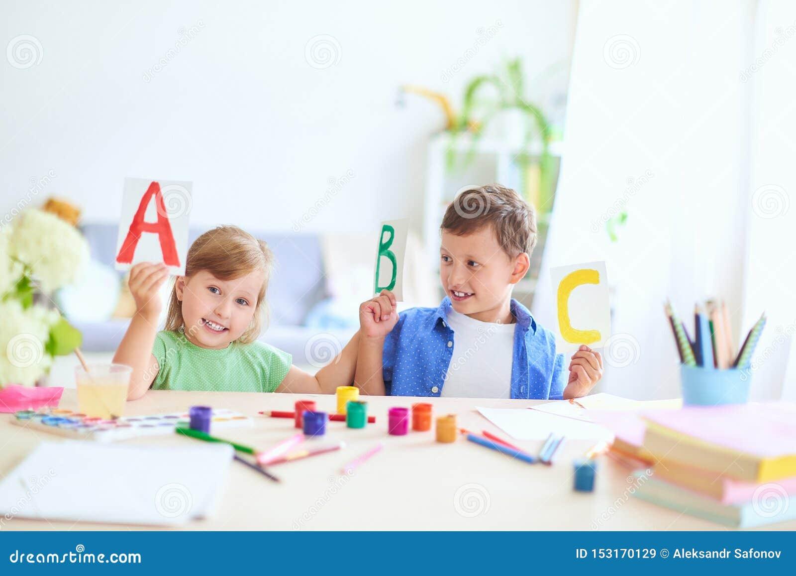 Una niña y un muchacho aprender en casa niños felices en la tabla con la sonrisa de las fuentes de escuela divertida y el aprendi
