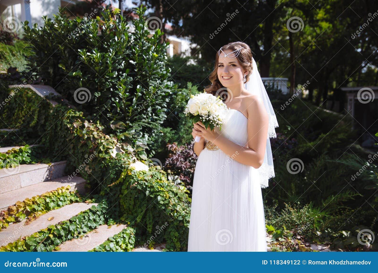 362cc9b84 Una novia embarazada de la clase europea presenta con un ramo de rosas  blancas