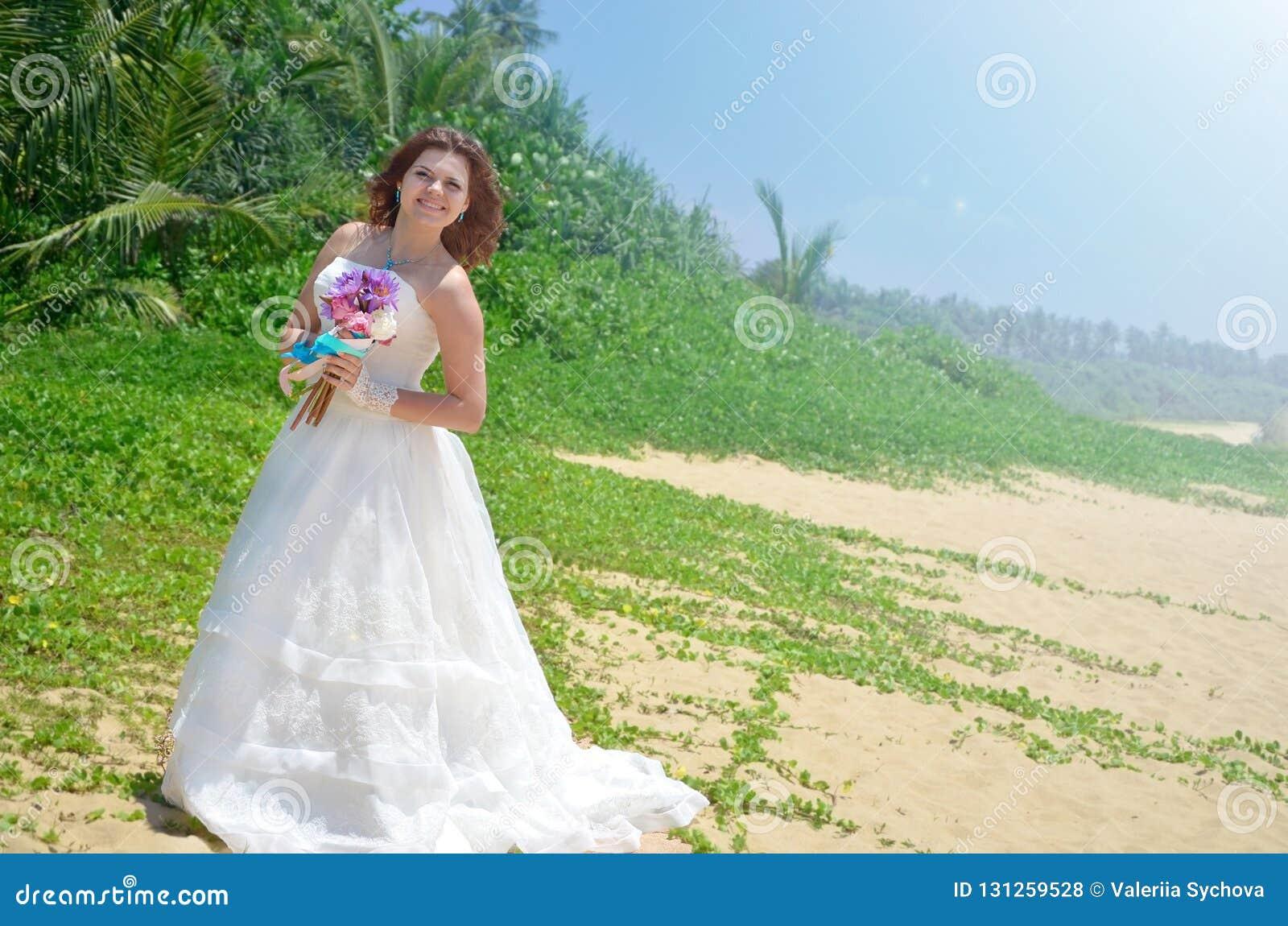 Una novia joven en un vestido airoso blanco se está colocando con un ramo de lotos muchacha que sonríe en una playa tropical en l