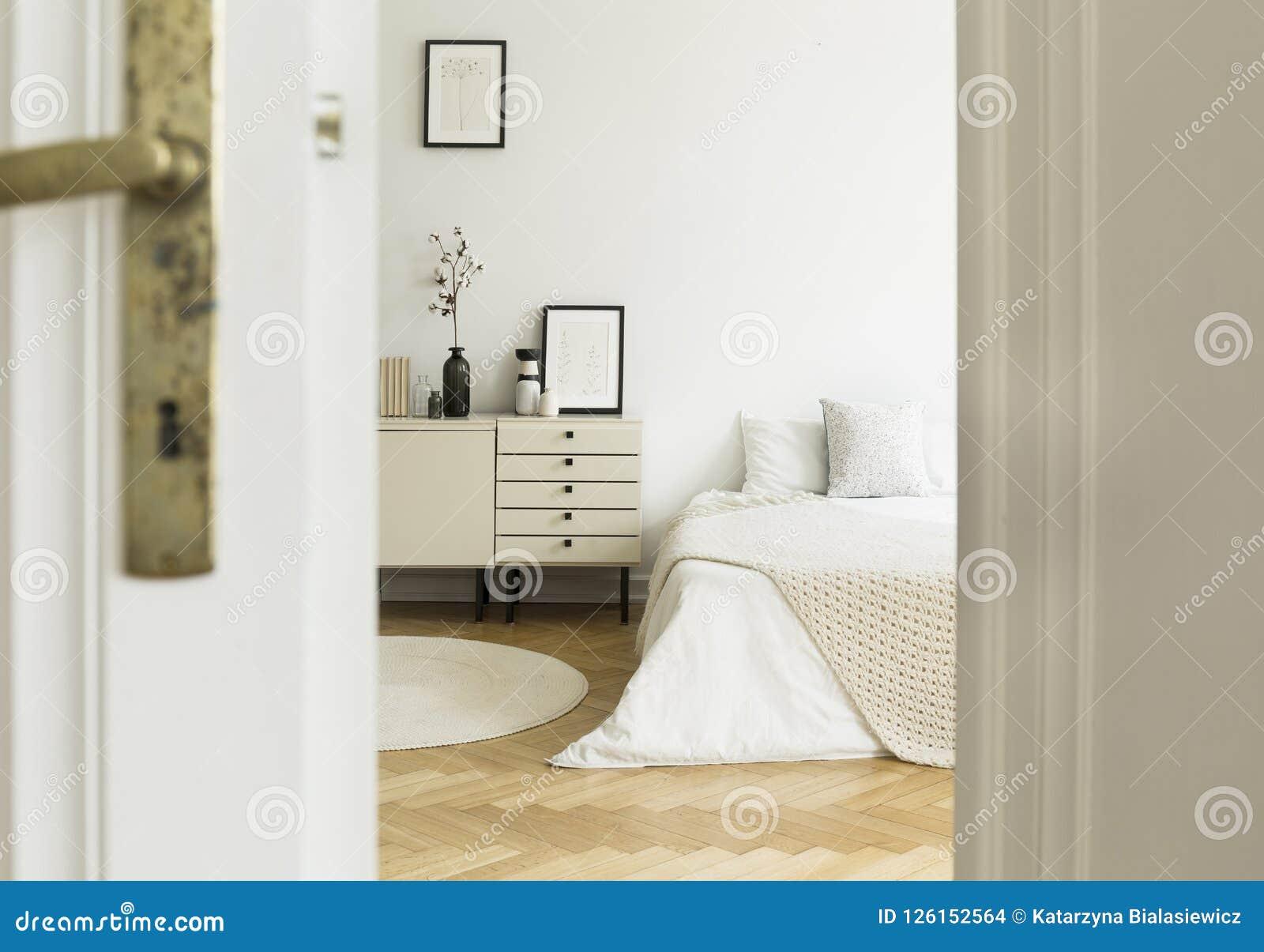 Una ojeada a través de una puerta en un interior monocromático, blanco del dormitorio con una cama y de los gabinetes que se colo