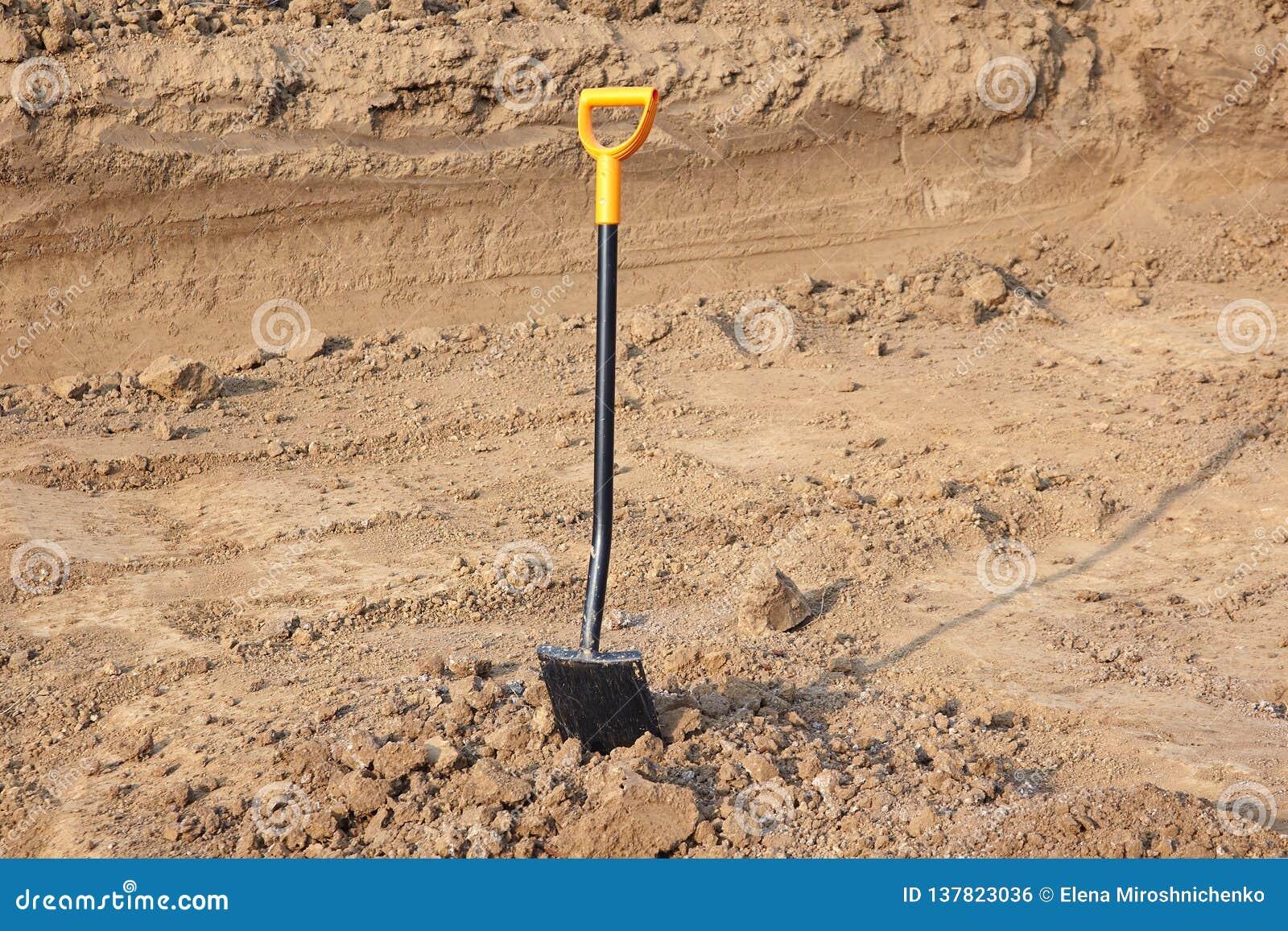 Una pala con la maniglia gialla luminosa attaccata alla terra Impianti frantumati, scavi