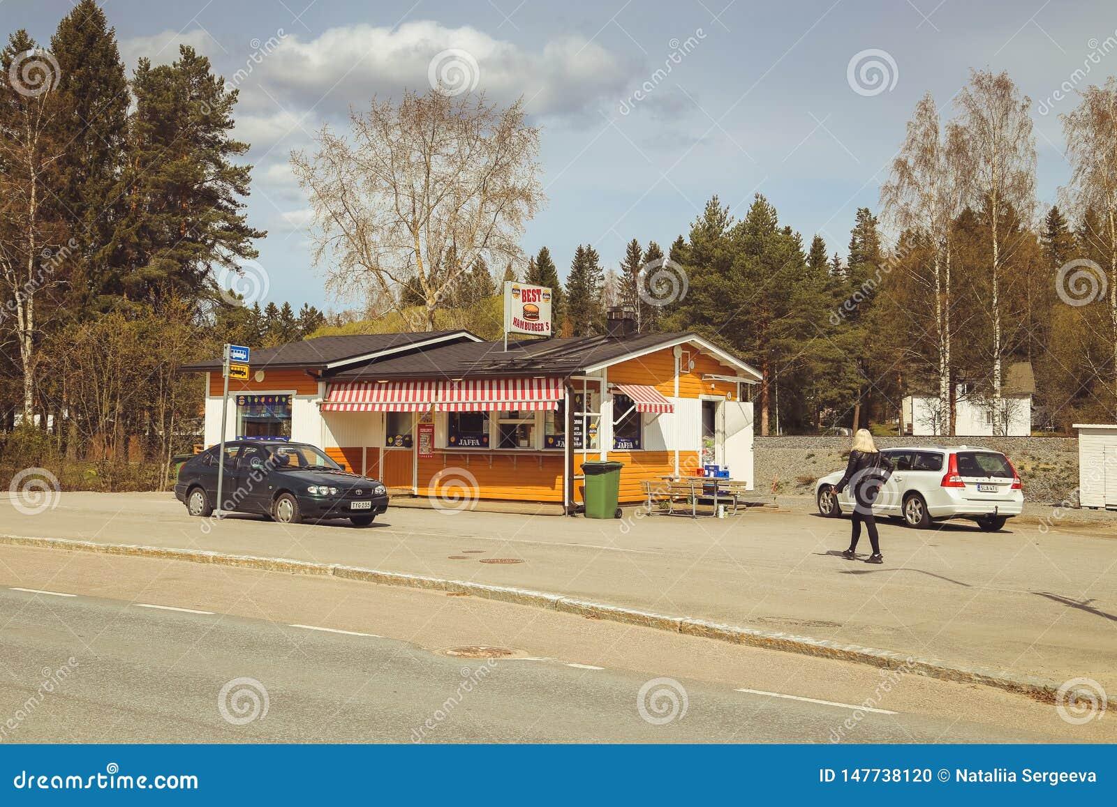 Una pequeña ciudad en Finlandia, un café del borde de la carretera, coches en el camino y tiendas Día de verano de la ciudad finl