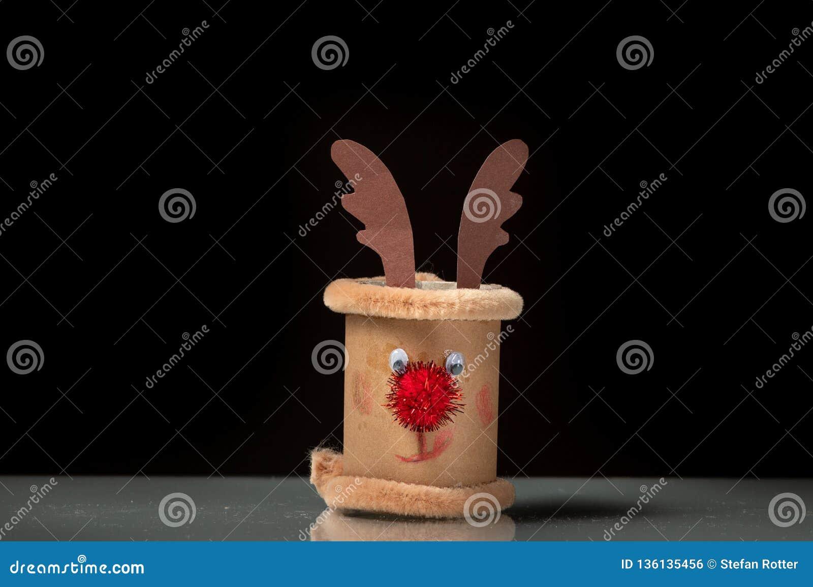 Una pequeña figura de un reno hecho de un rollo del papel higiénico por un niño