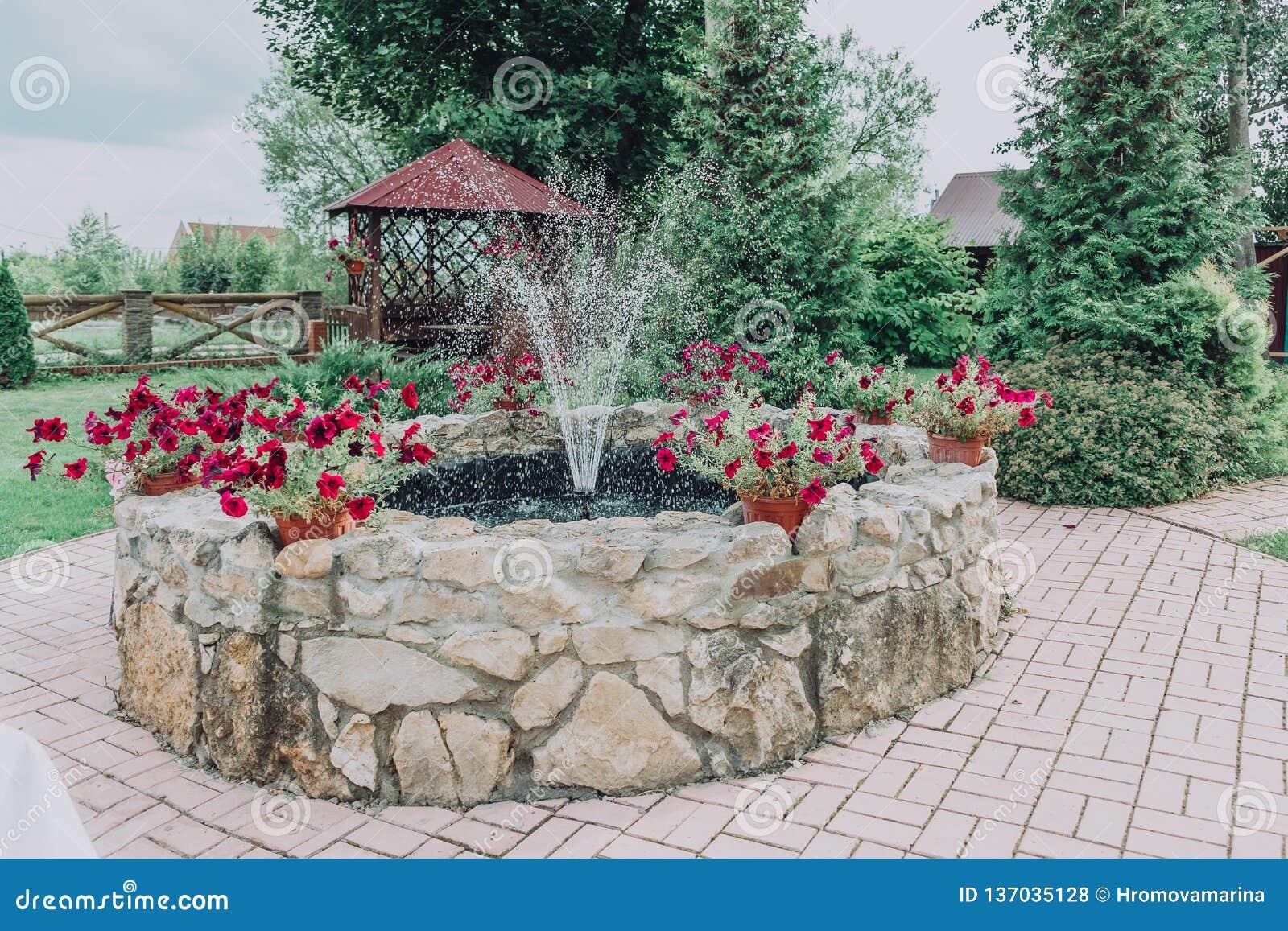 Una Pequeña Fuente En El Jardín De La Piedra Con Las Flores De La ...