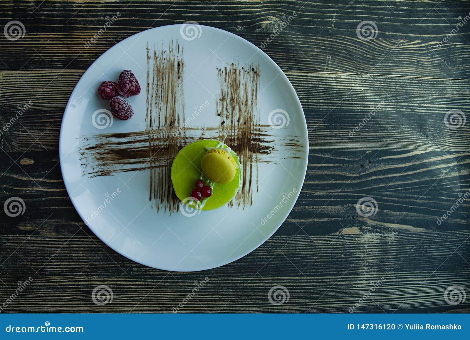 Una pequeña torta del pistacho con una capa verde y adornada con el viburnum, preparación de la confitería en un fondo negro Vist