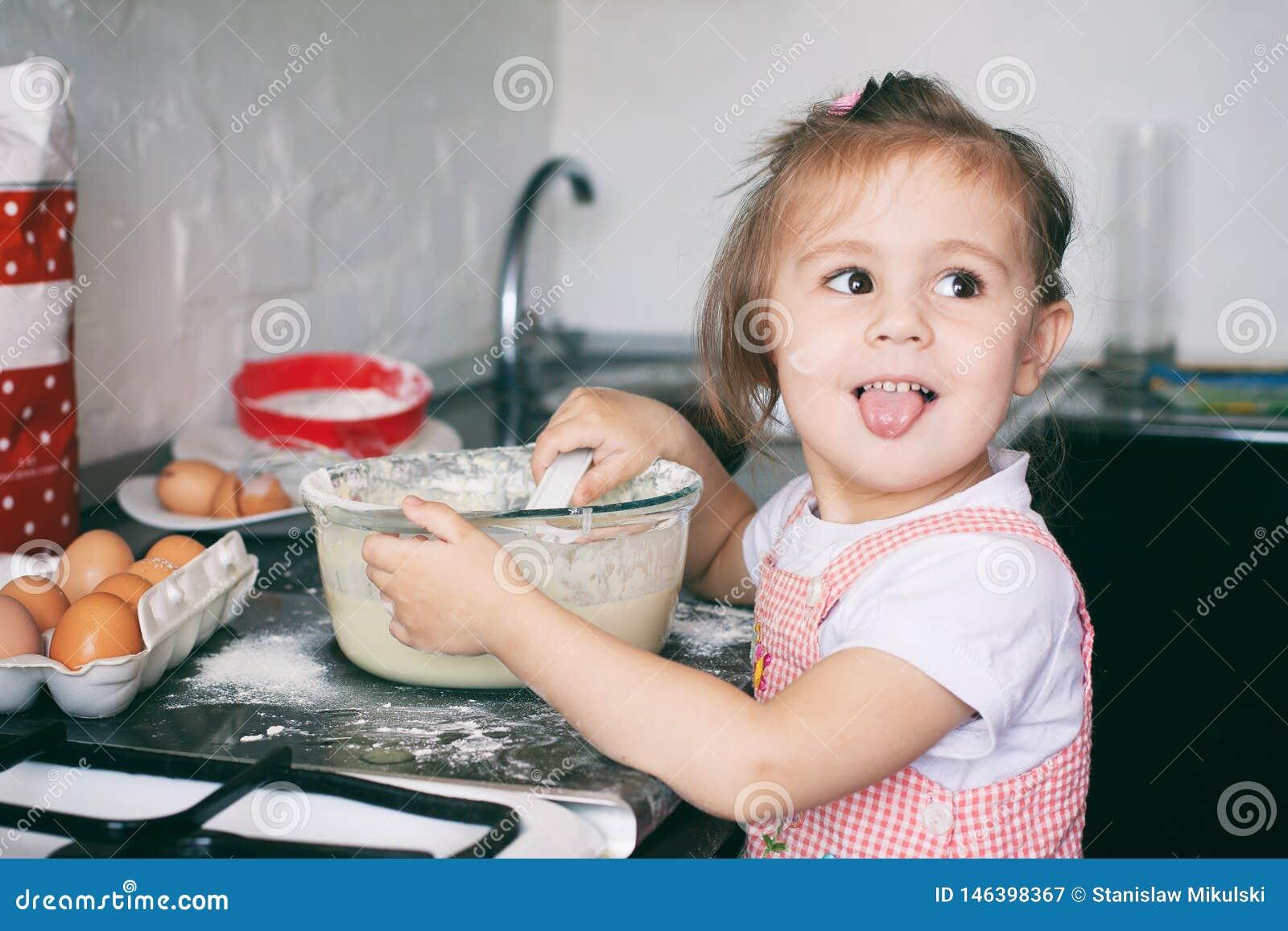 Una peque?a muchacha linda que prepara la pasta en la cocina en casa