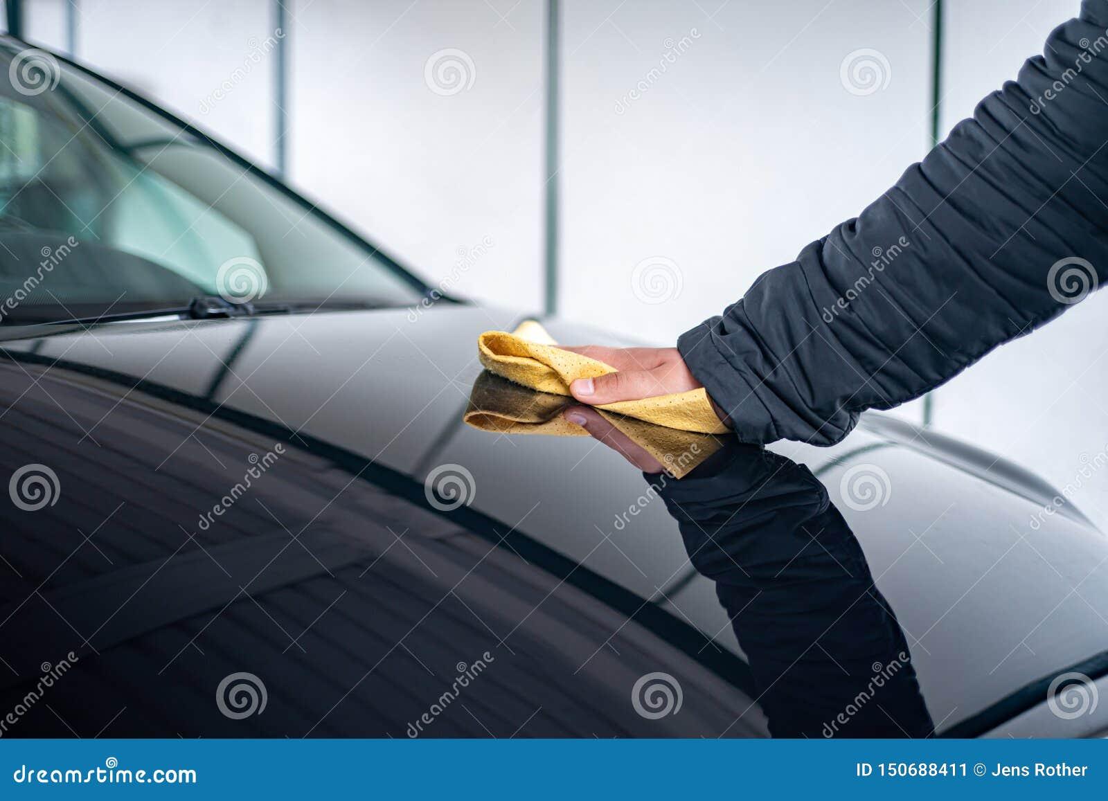 Una persona pule el capo en su coche