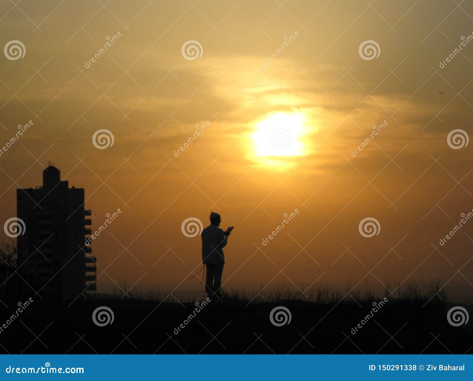 Una persona religiosa ruega a dios en una colina delante del sol y de la puesta del sol