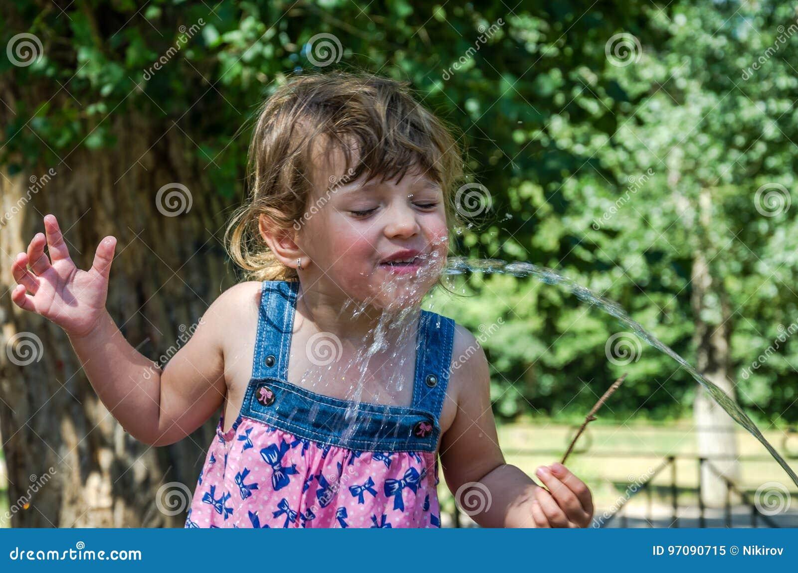 Una piccola bambina adorabile, un bambino in un vestito, bevande innaffia da un becco di una fontanella romana un giorno di estat