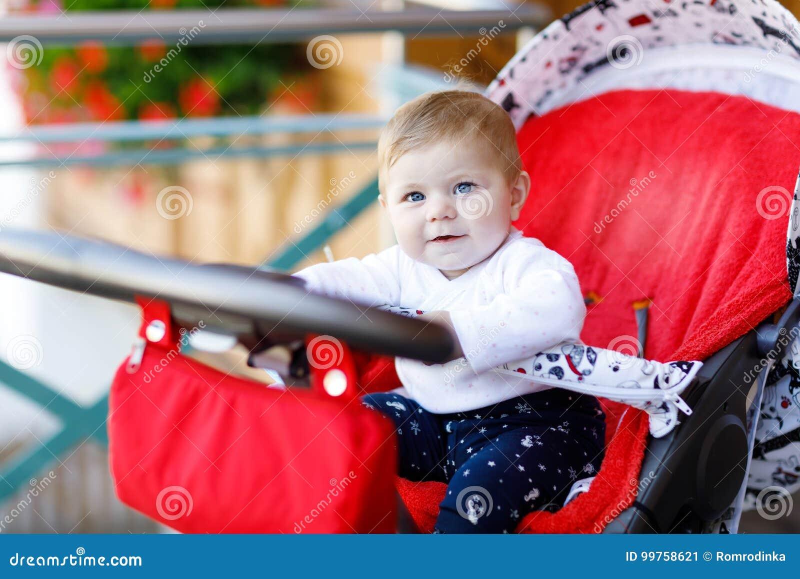 Una piccola bella neonata sveglia di 6 mesi che si siedono nella mamma della carrozzina o del passeggiatore ed aspettare