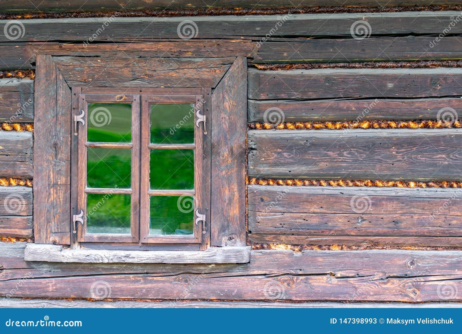 Una piccola finestra nella parete di vecchia casa di legno
