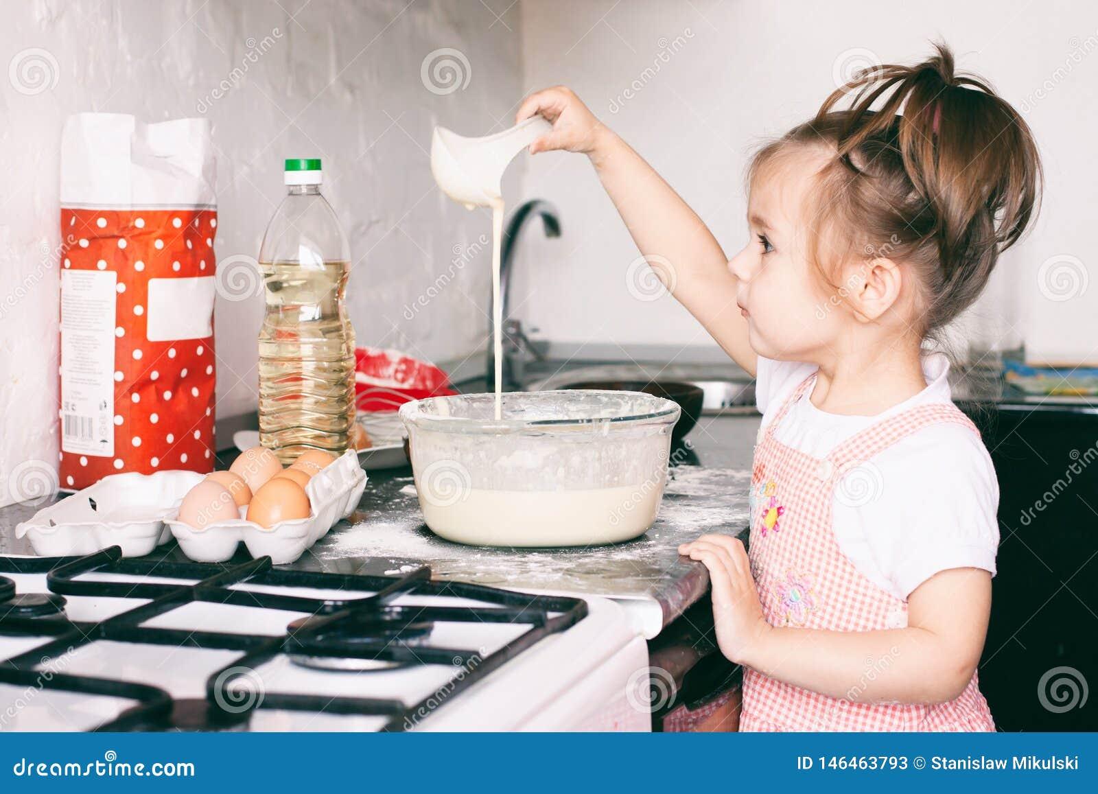 Una piccola ragazza sveglia che prepara la pasta nella cucina a casa