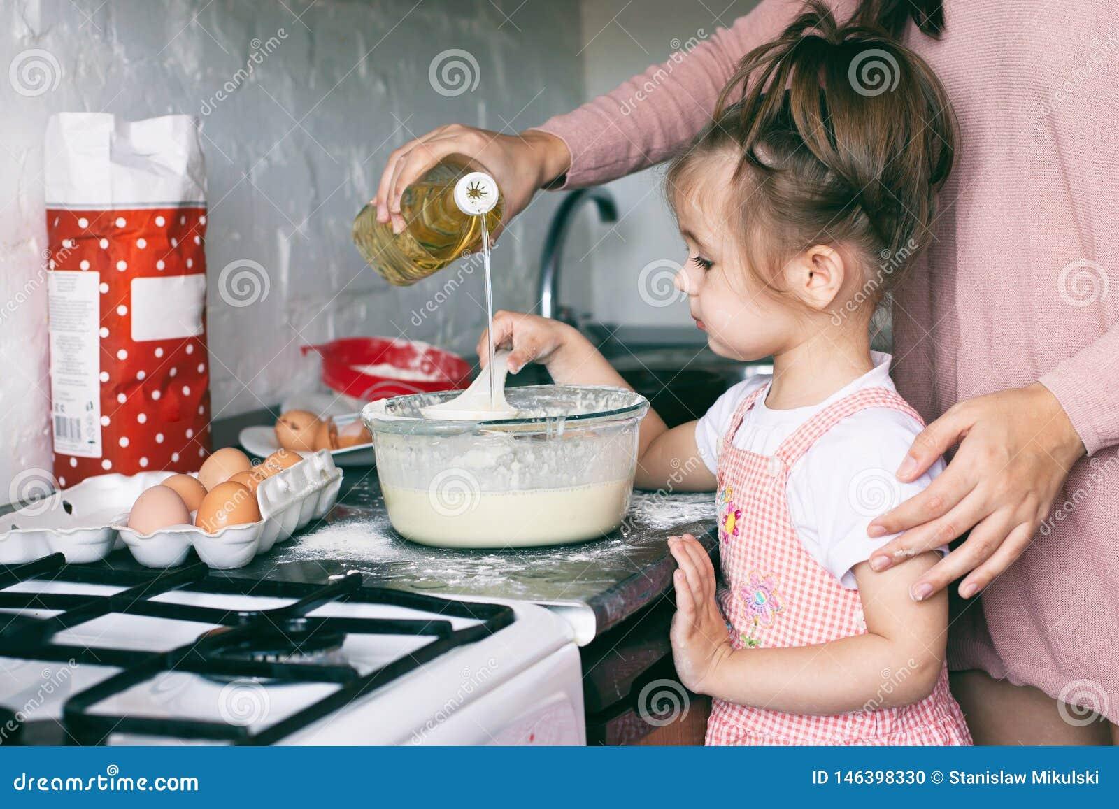 Una piccola ragazza sveglia e sua madre che preparano la pasta nella cucina a casa