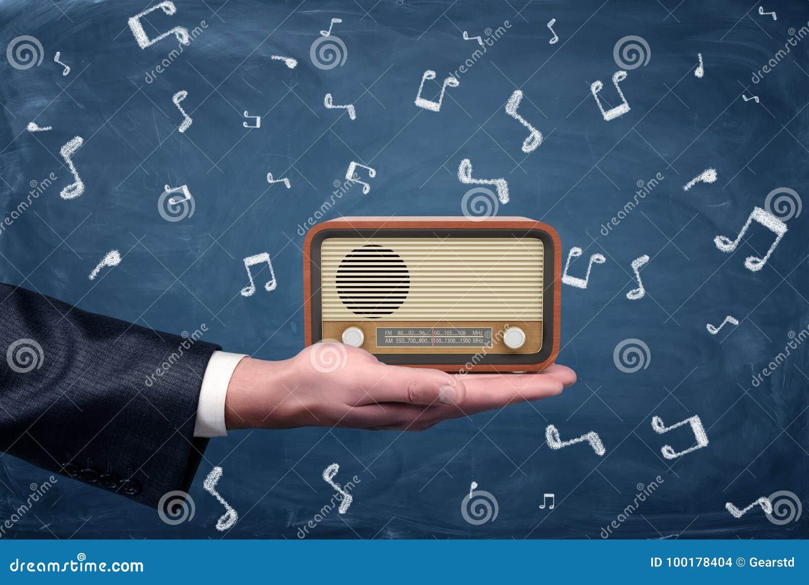 Una piccola retro radio con alloggio marrone e supporti anteriori gialli su una palma del ` s dell uomo d affari sul fondo della