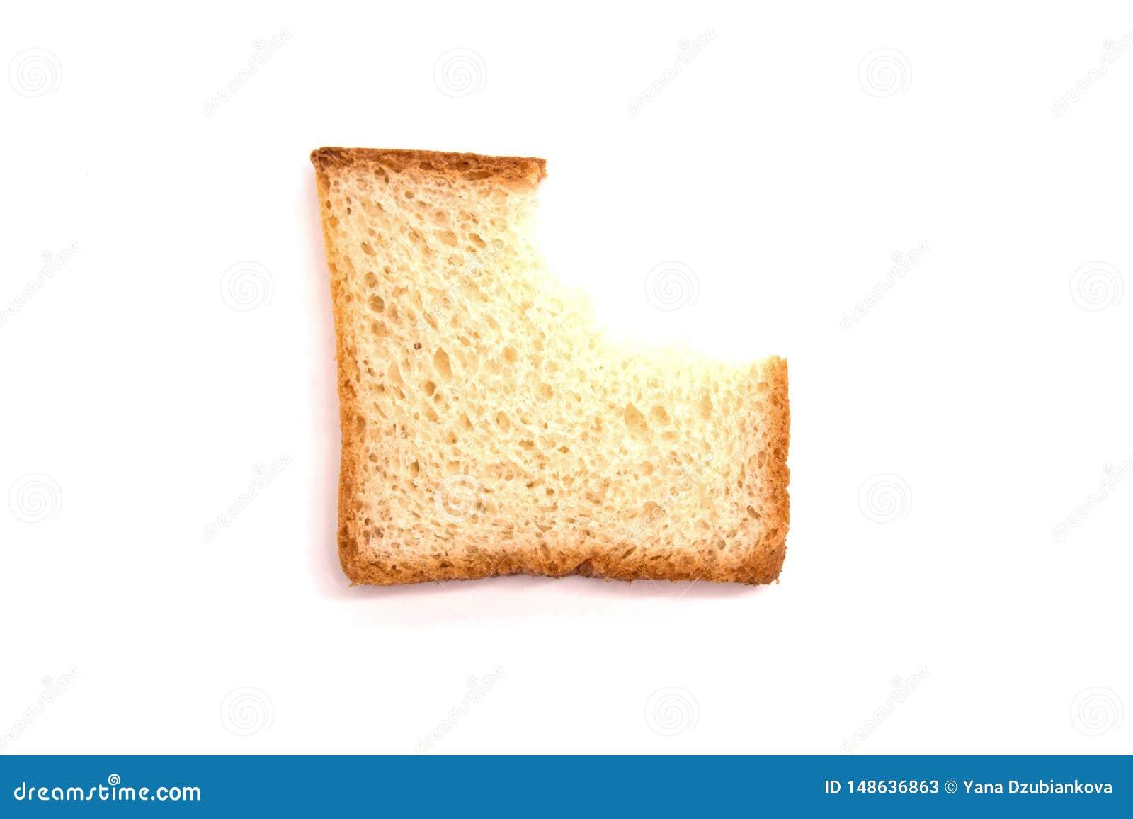Una pieza del pan blanco de la tostada mordido en el fondo blanco