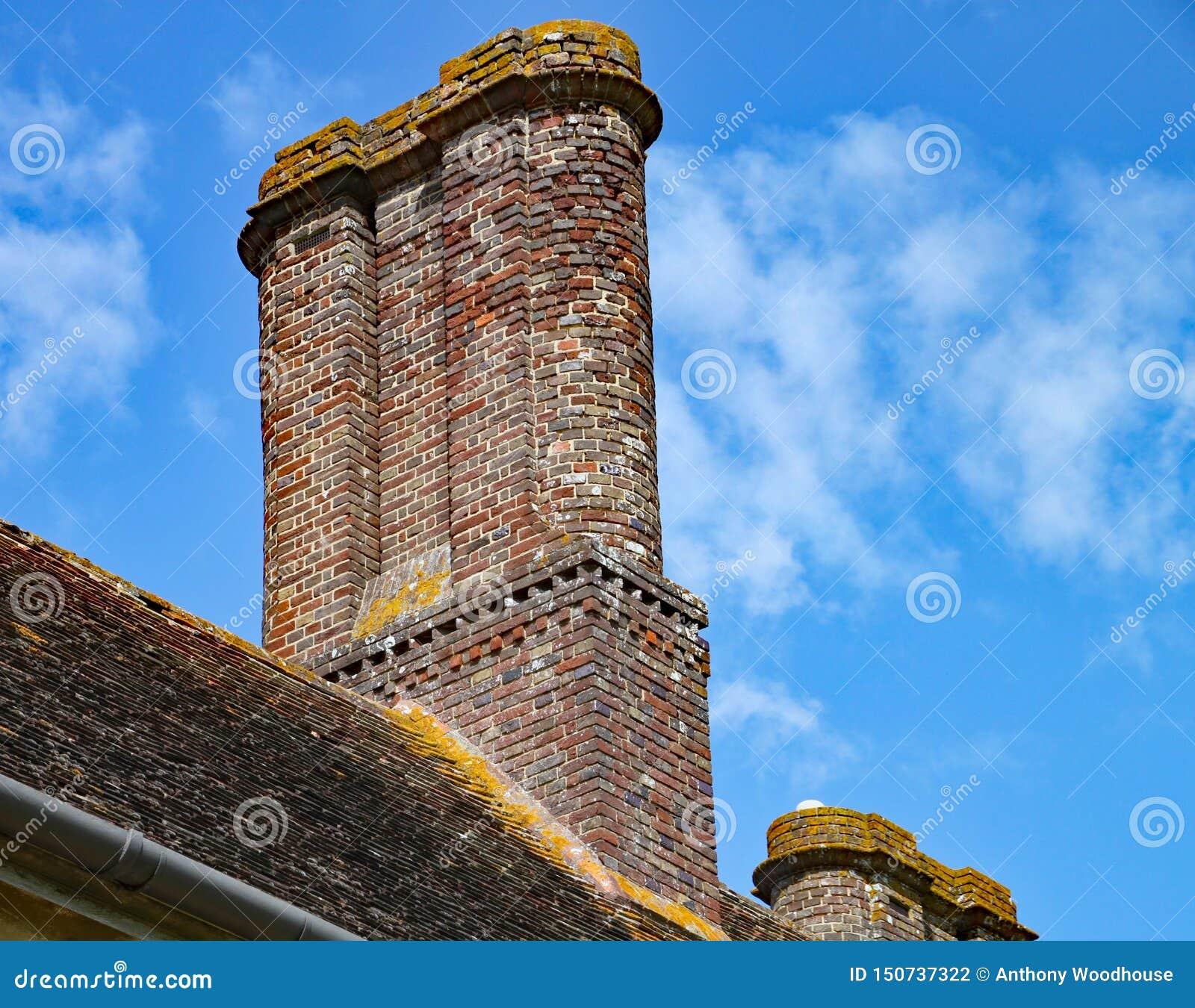 Una pila de chimenea vieja del ladrillo encima de una casa inglesa vieja
