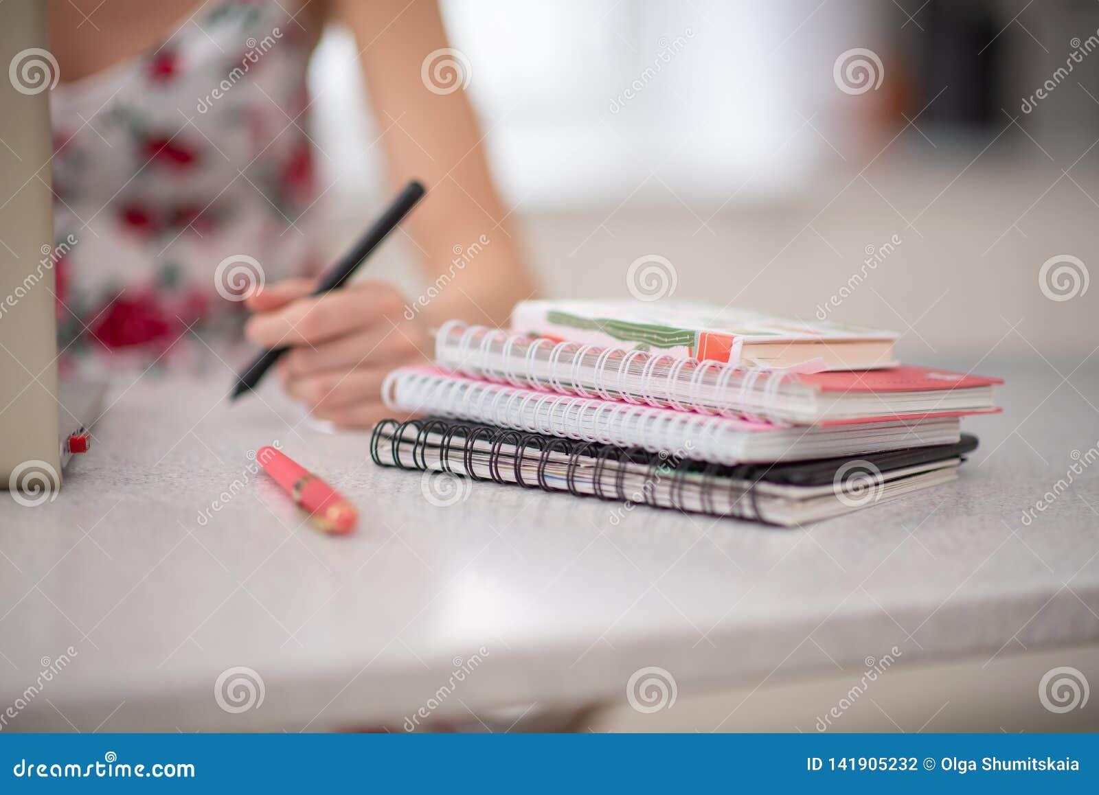 Una pila de cuadernos espirales y de estudiante en el ordenador portátil