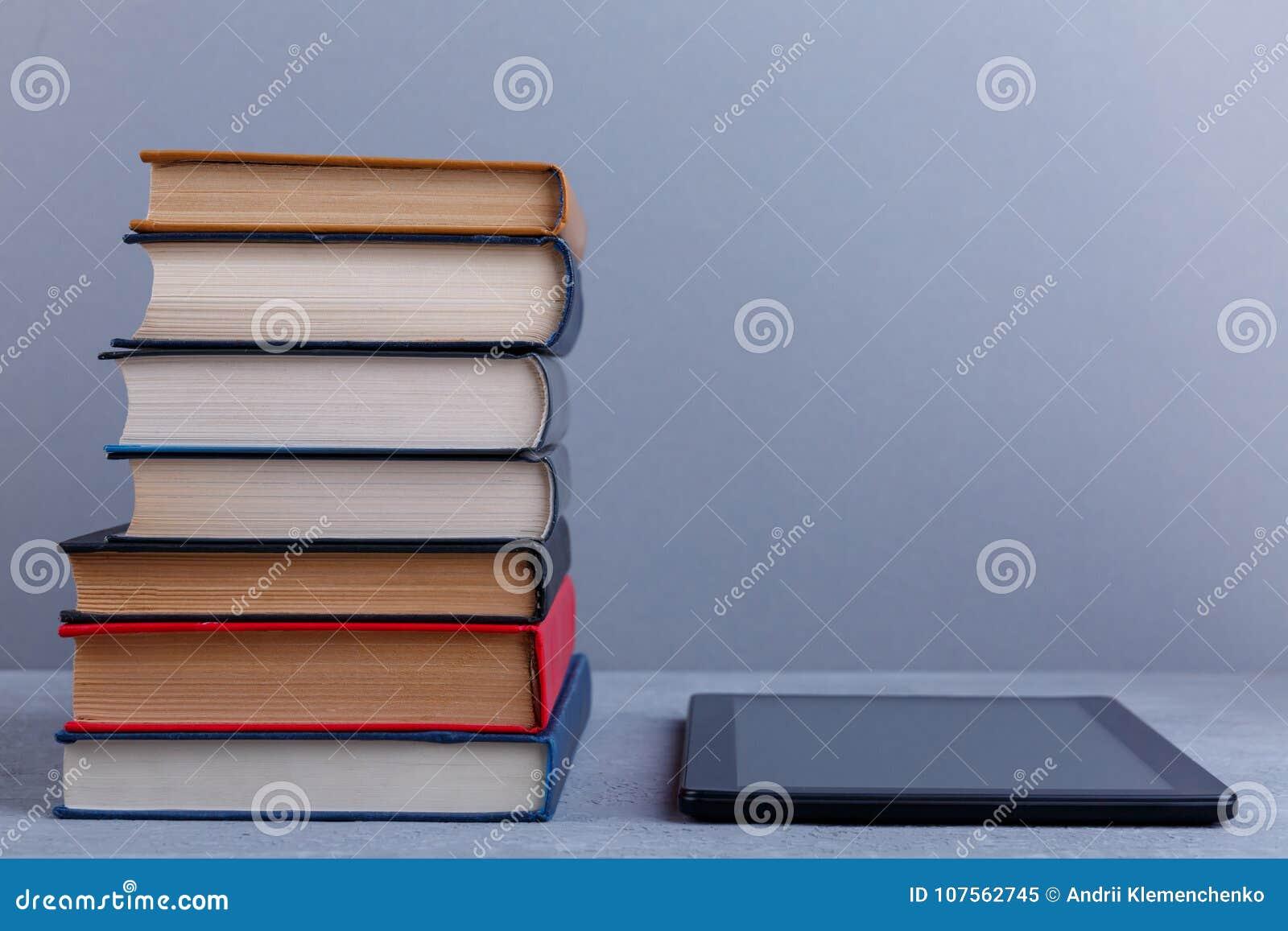 Una pila de libros y de una tableta después El concepto de educación foreground