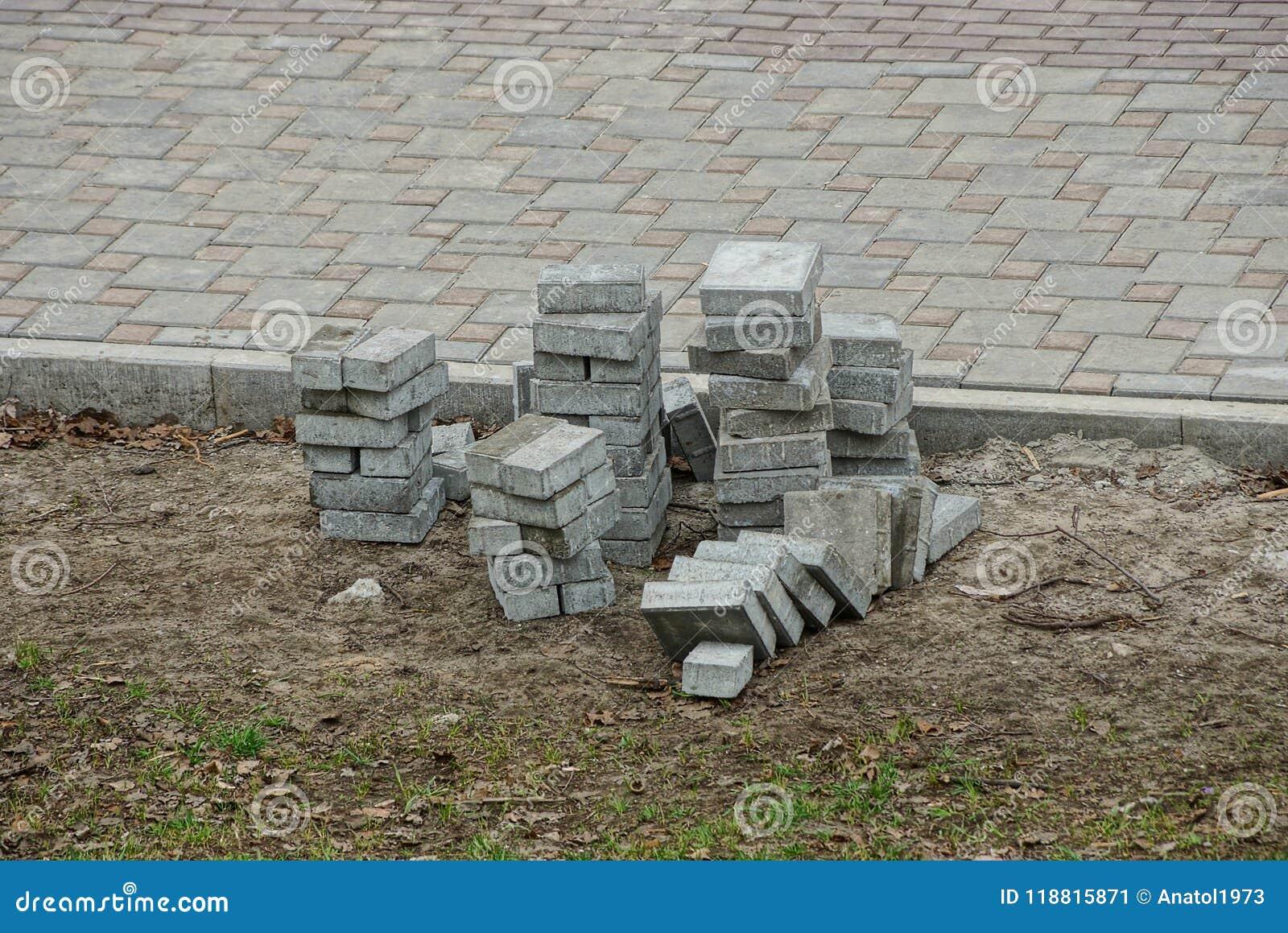 Una pila de pavimentar las tejas grises en la tierra cerca del camino