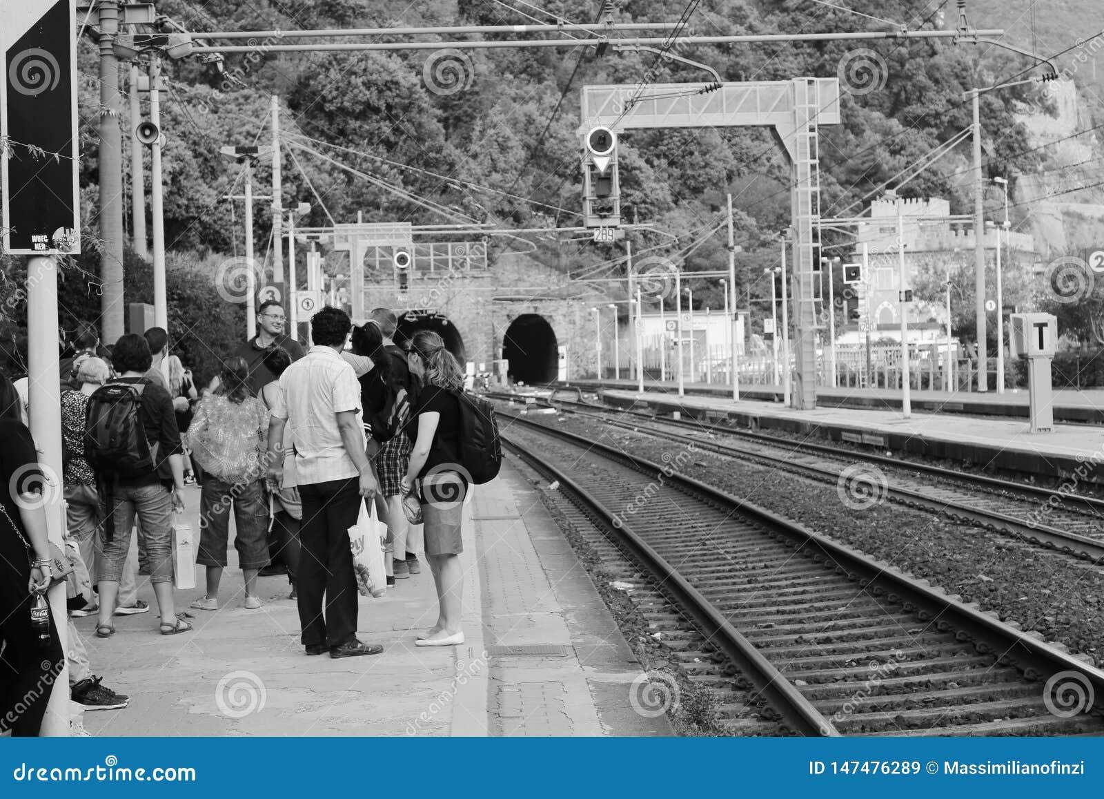 Una plataforma apretada con los pasajeros que esperan para los acercamientos del servicio de tren local del túnel en el ferrocarr