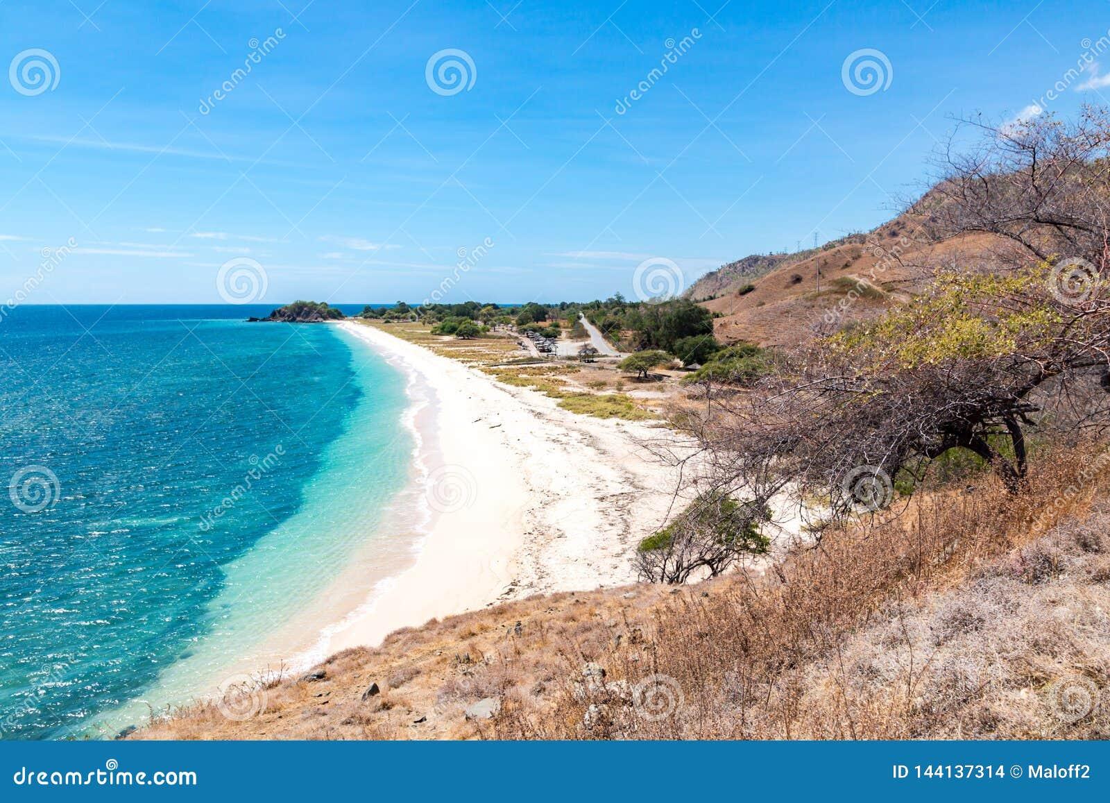 Una playa del dólar Playa arenosa amarilla de Idillic de Timor Oriental, Timor-Leste Costa costa con las colinas, las montañas y