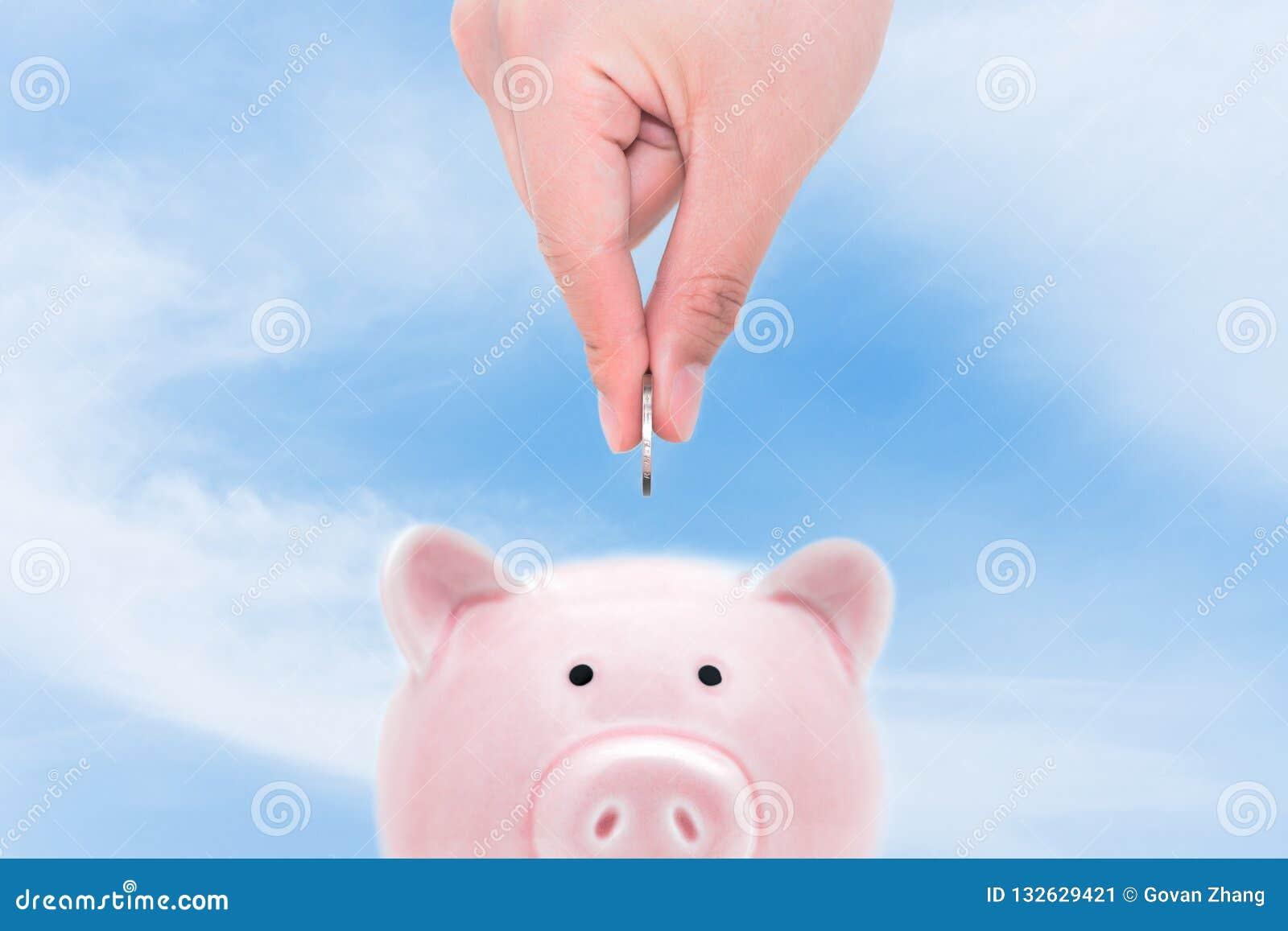 Una poder de los ahorros debajo del cielo azul y las nubes blancas y una mano que sostiene monedas