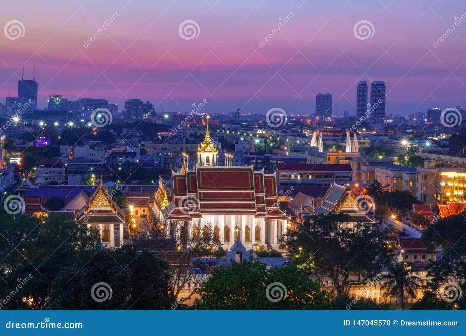 Una puesta del sol colorida con una hermosa vista sobre Bangkok y un templo en el frente