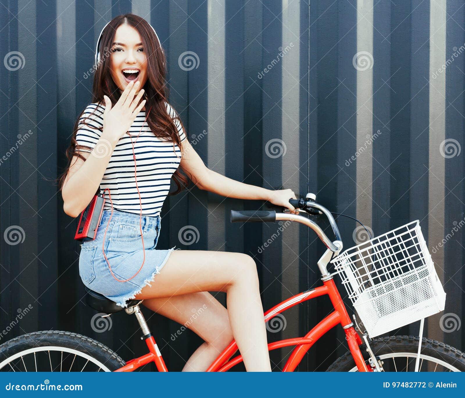 Una ragazza asiatica sbalorditiva in un attrezzatura dell estate, in una gonna del denim, con un giranastri e le cuffie si siede