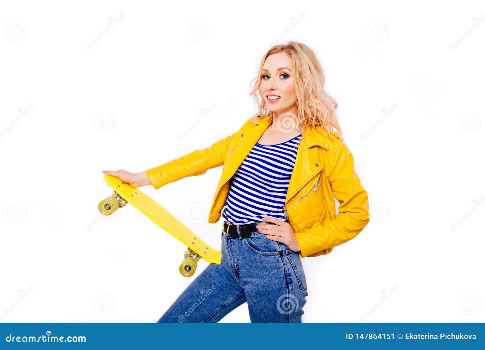 Una ragazza bionda snella con un pattino giallo in sue mani su un fondo bianco isolato