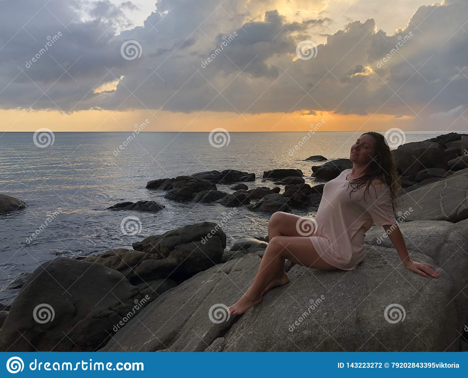 Una ragazza castana dalla carnagione chiara in vestiti leggeri della spiaggia si siede sulle pietre della linea costiera della sp
