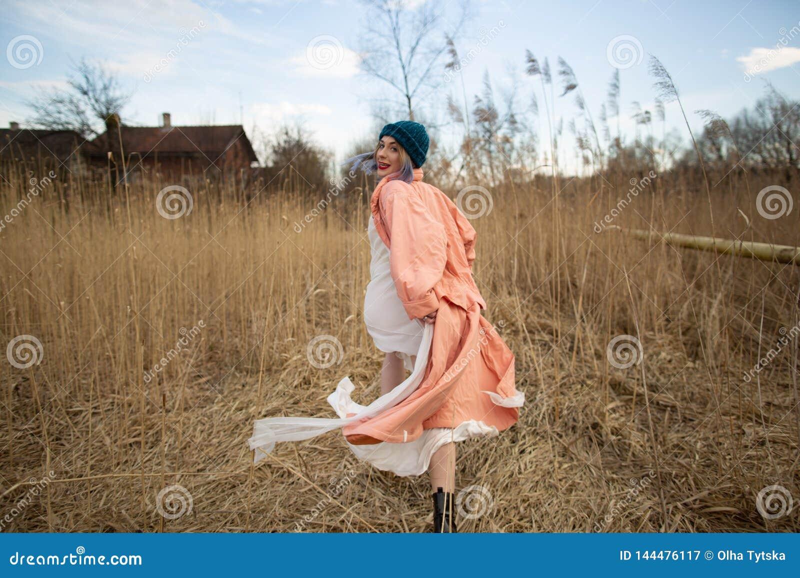 Una ragazza che porta un cappotto pastello e un cappello alla moda posa in un giacimento di grano Viev posteriore