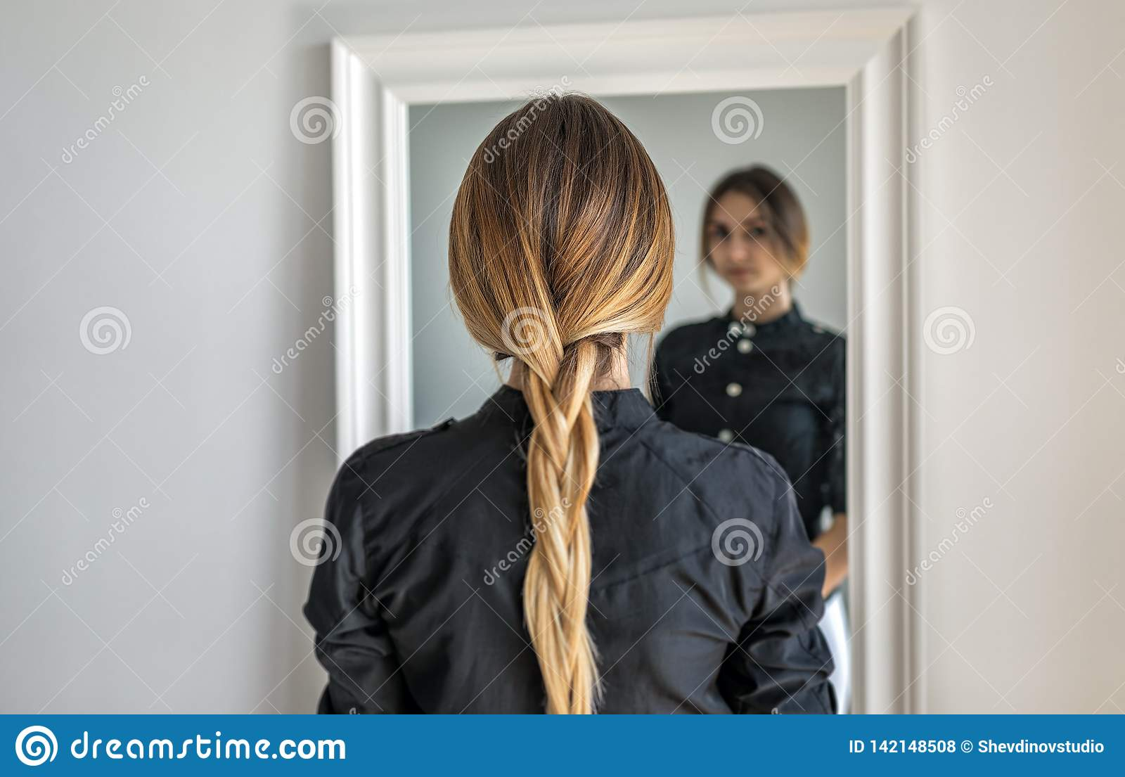 Una ragazza con capelli biondi lunghi intrecciati in una treccia sta stando all interno di fronte allo specchio