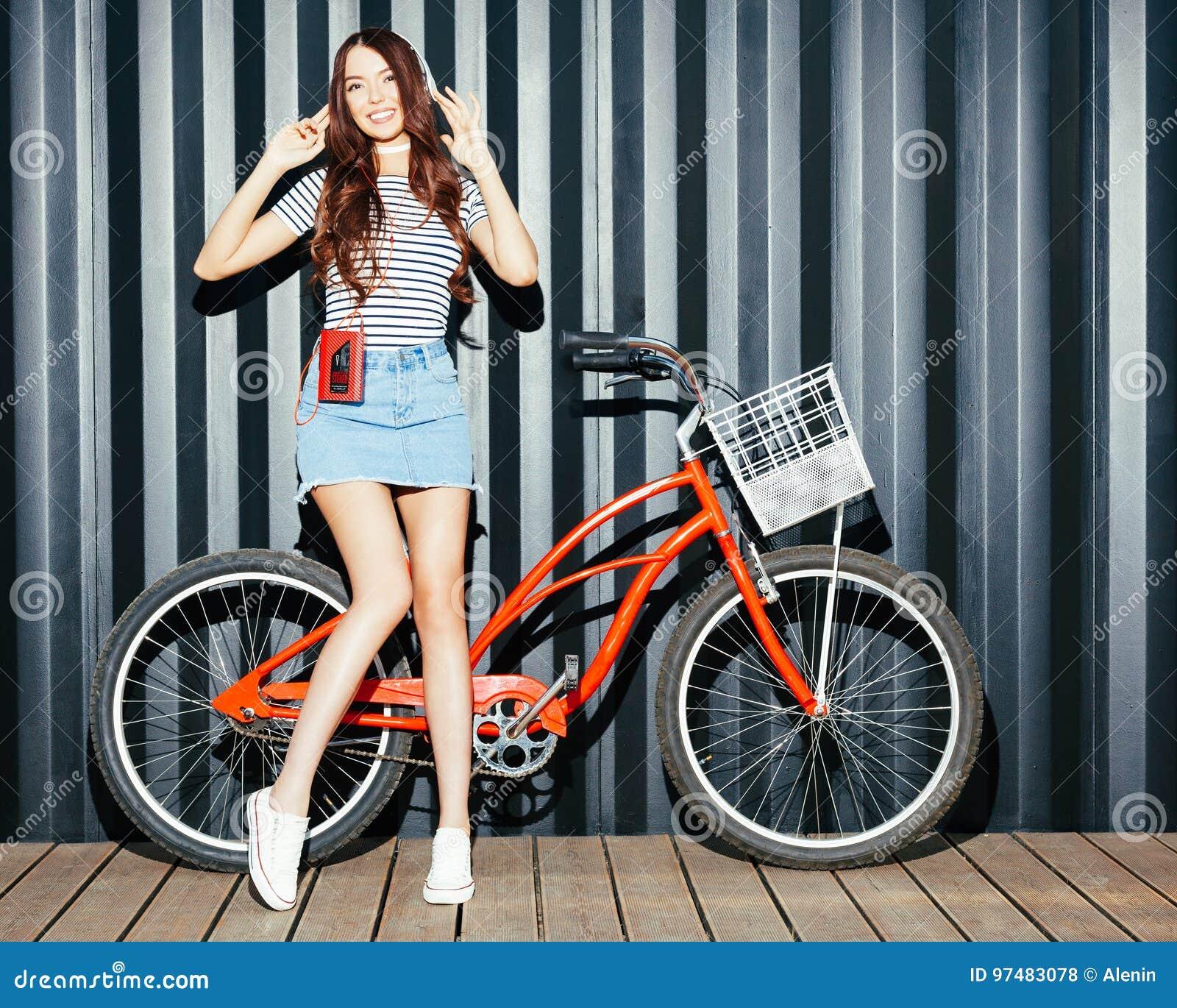 Una ragazza con le gambe lunghe sbalorditiva, una donna asiatica in un attrezzatura di estate, una gonna del denim, con un girana