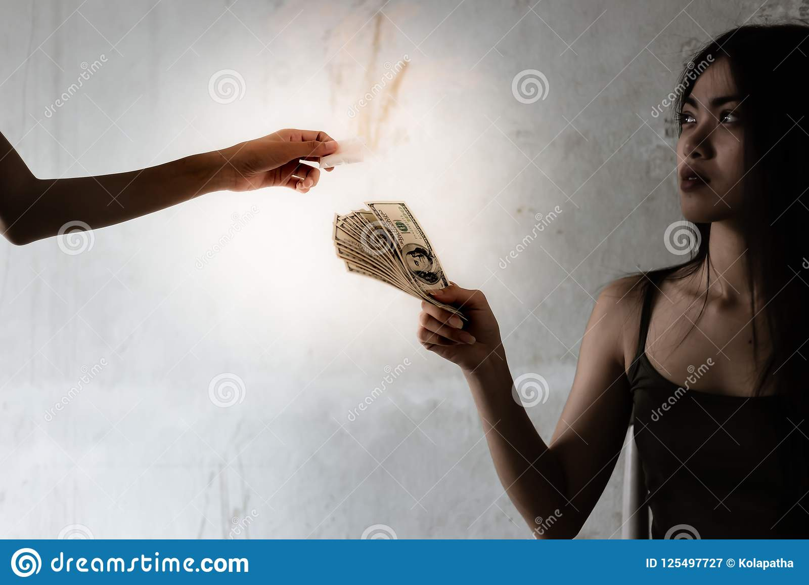 Una ragazza del drogato sta dando i soldi dei dollari ad un trafficante di droga per buyin