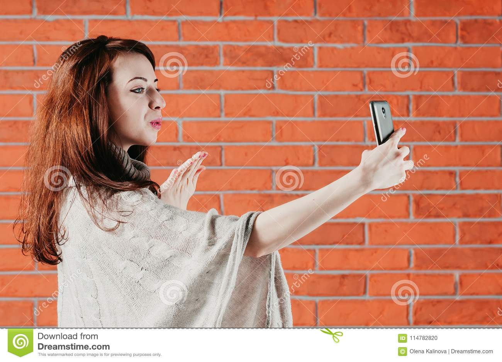 Una ragazza graziosa sta facendo il selfie con lo smartphone, inviante il bacio dell aria