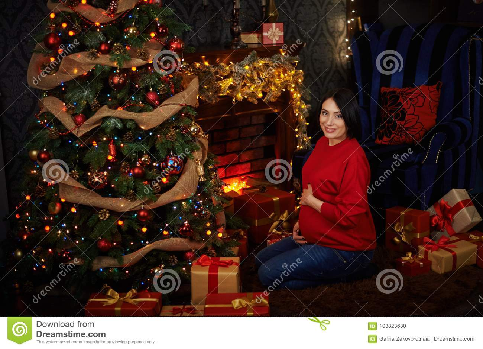 Una ragazza incinta veste un albero di Natale