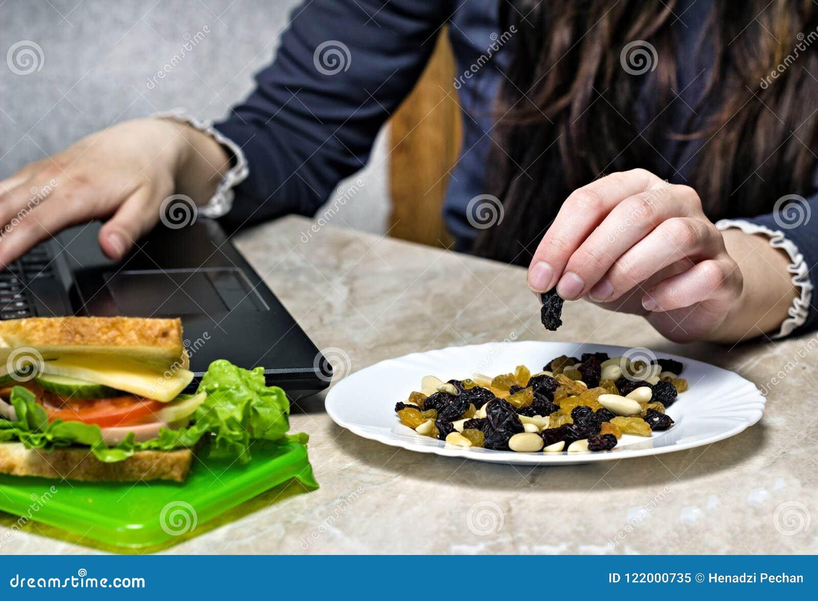 Una ragazza lavora dietro un computer portatile e prende dai frutti secchi piatto, un panino, uno spuntino sul lavoro, primo pian