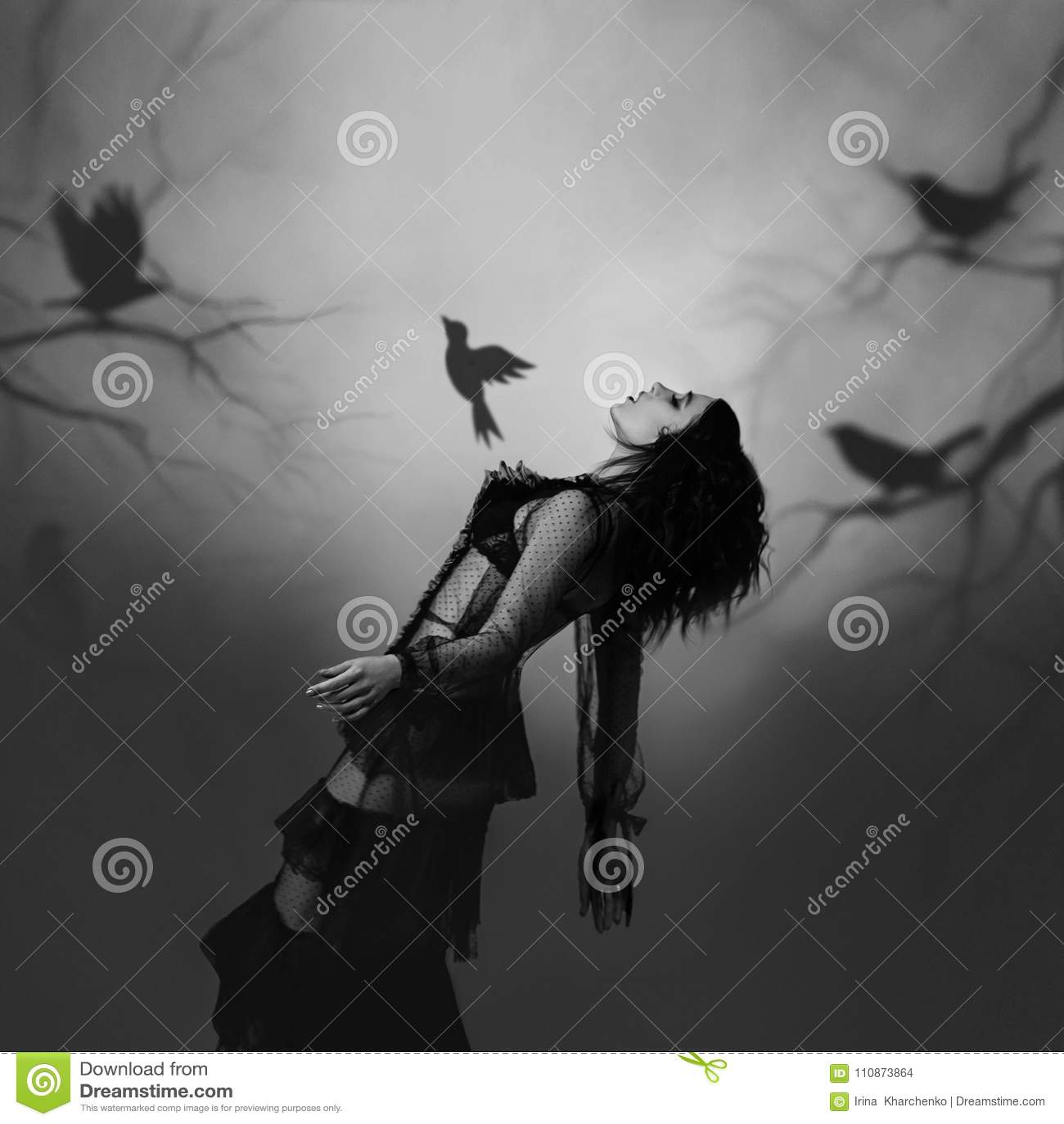 Una ragazza nel nero, vestito d annata che posa contro lo sfondo di una foresta triste, che è creata dal proiettore