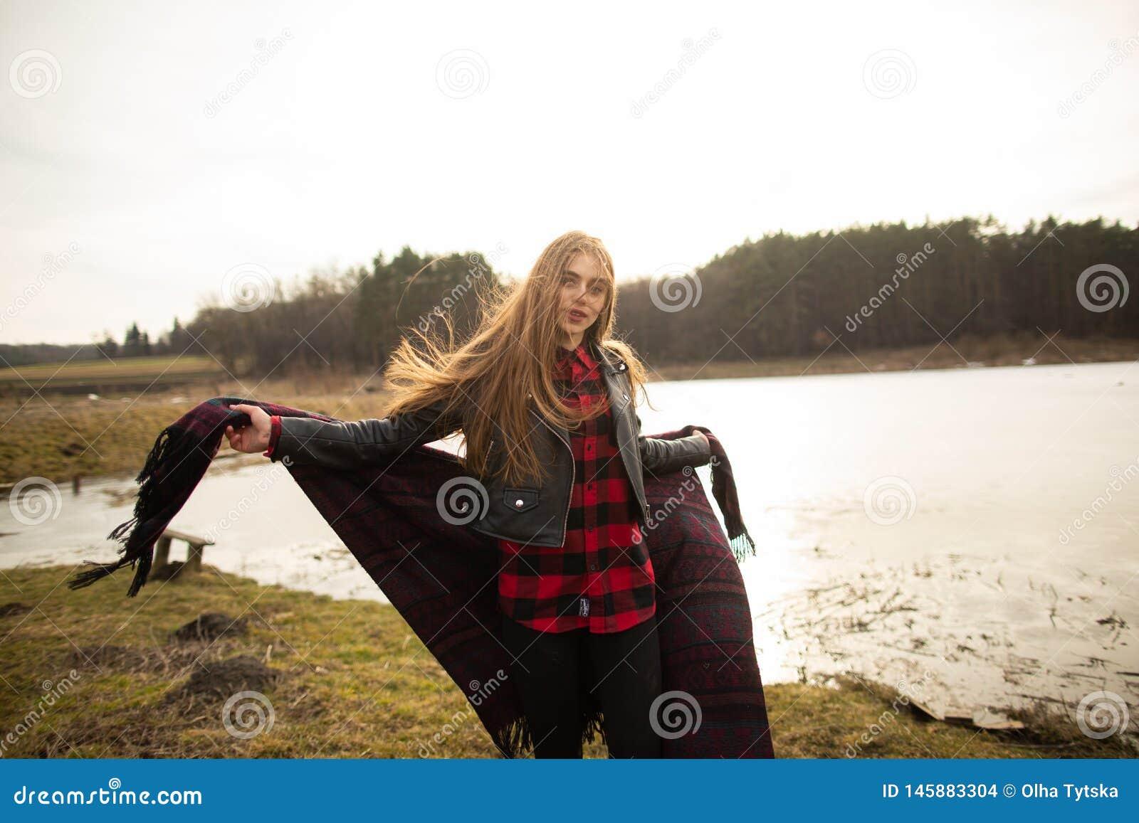 Una ragazza posa sulla riva di un lago, gettante una sciarpa lei
