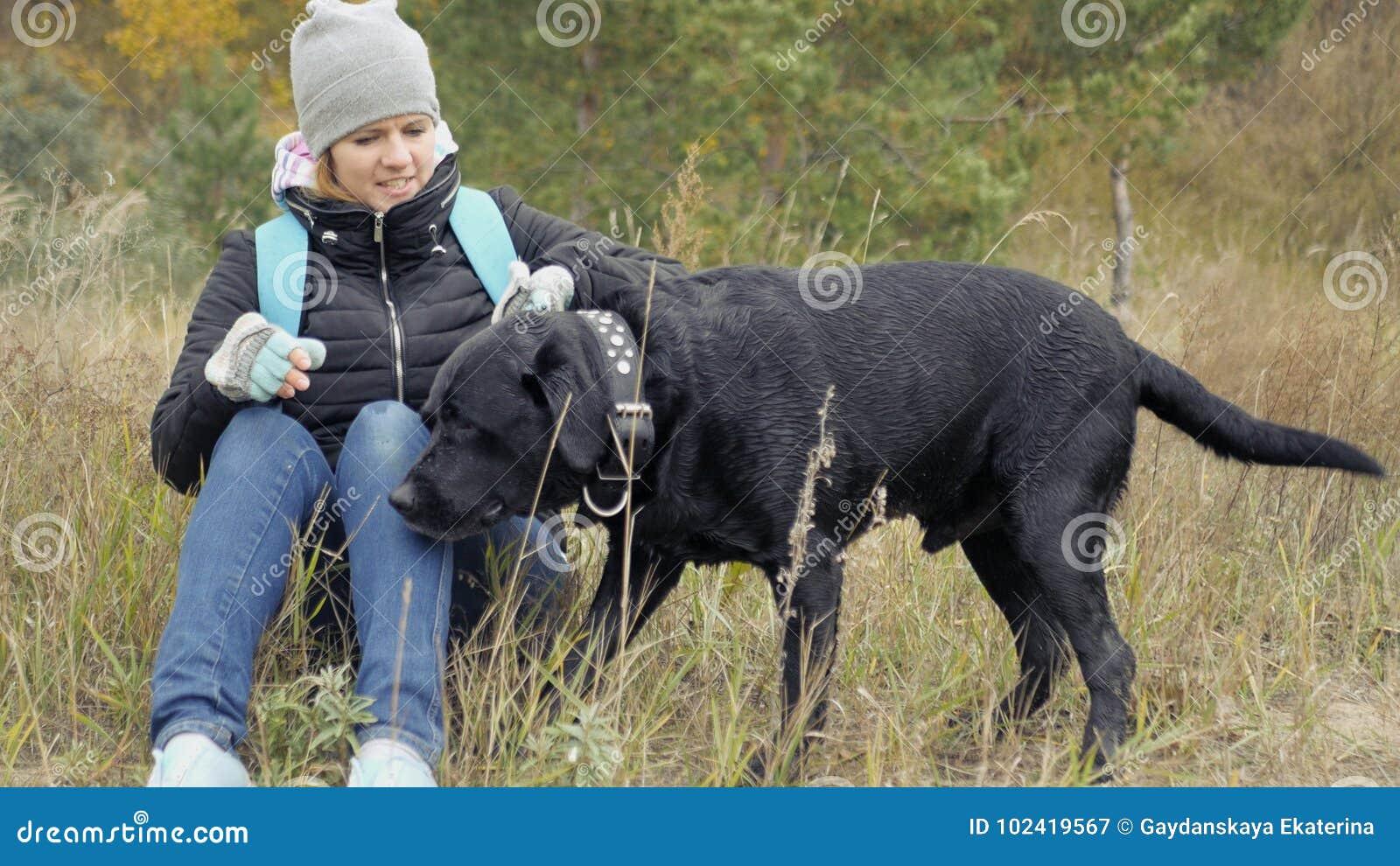 Una ragazza prende il suo cane per il collare e vuole mettere il suo vicino foto