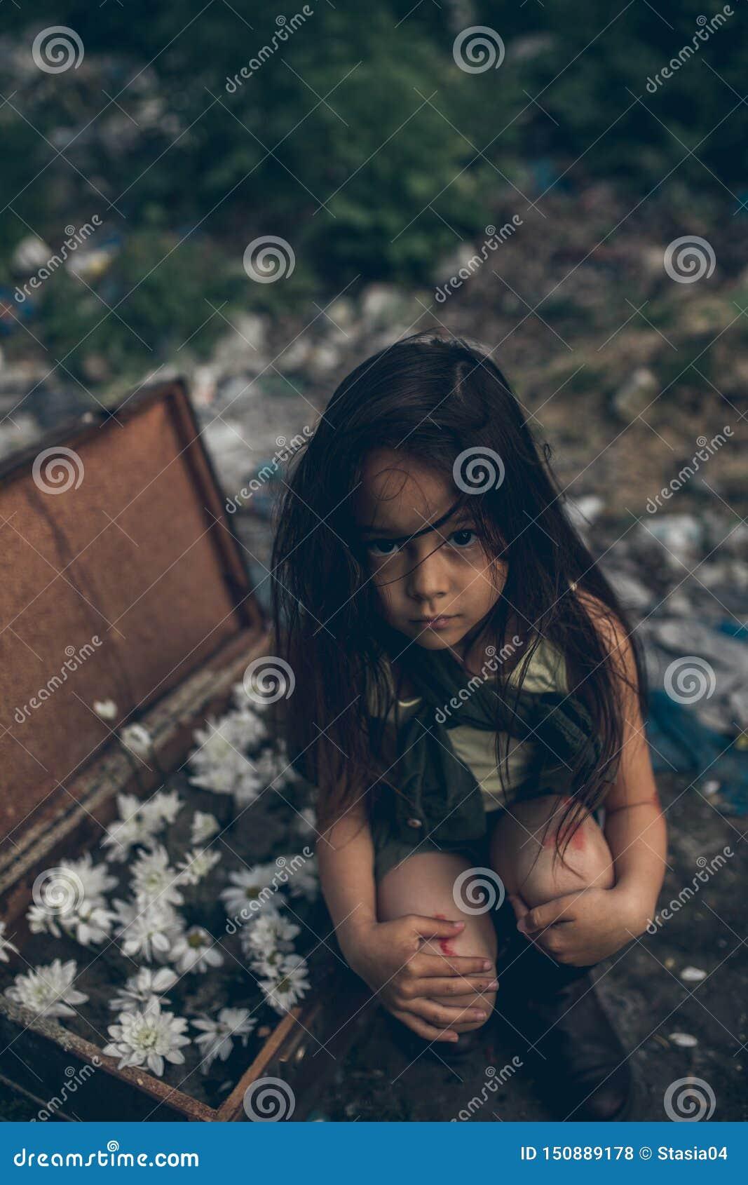 Una ragazza senza tetto sta sedendosi su una discarica accanto ad una valigia con i fiori dentro