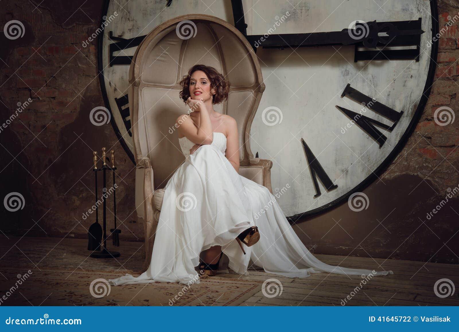 Una ragazza sorridente in un vestito da sposa in sedia sconosciuta La sposa in una sedia sui precedenti degli orologi e del set d