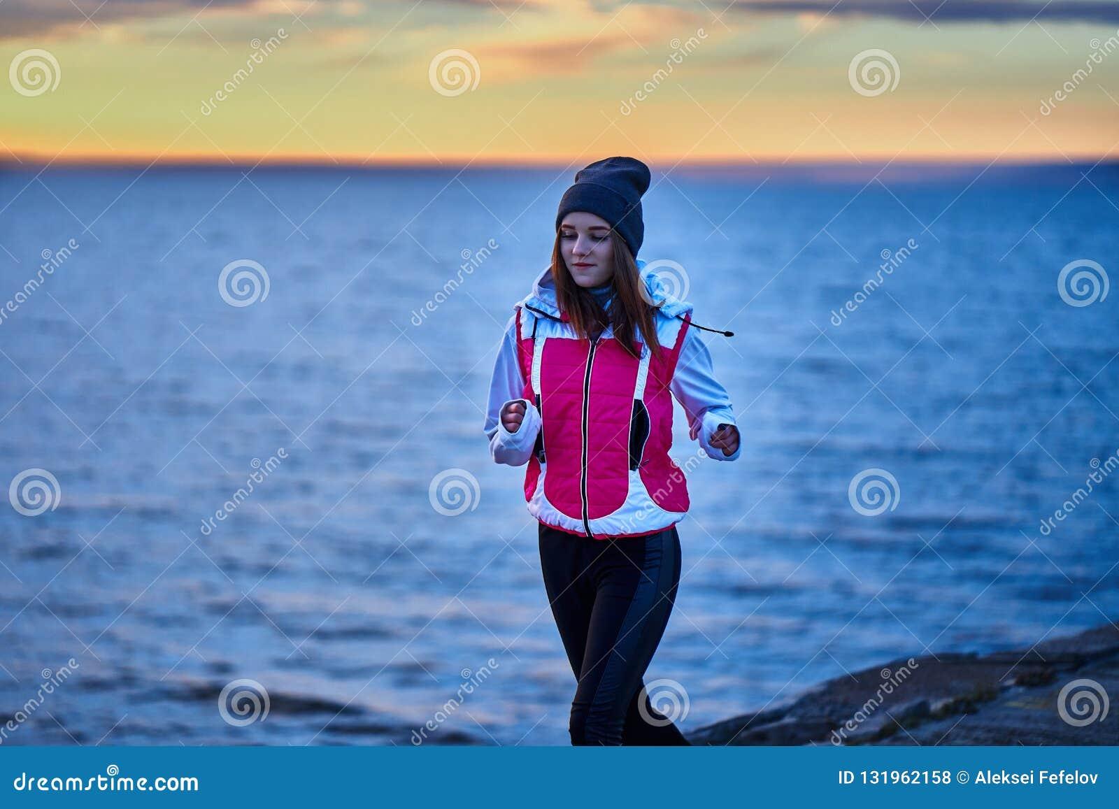 Una ragazza in sport cappello e rivestimento fa un trotto di mattina sull argine di mattina prima dell alba del sole