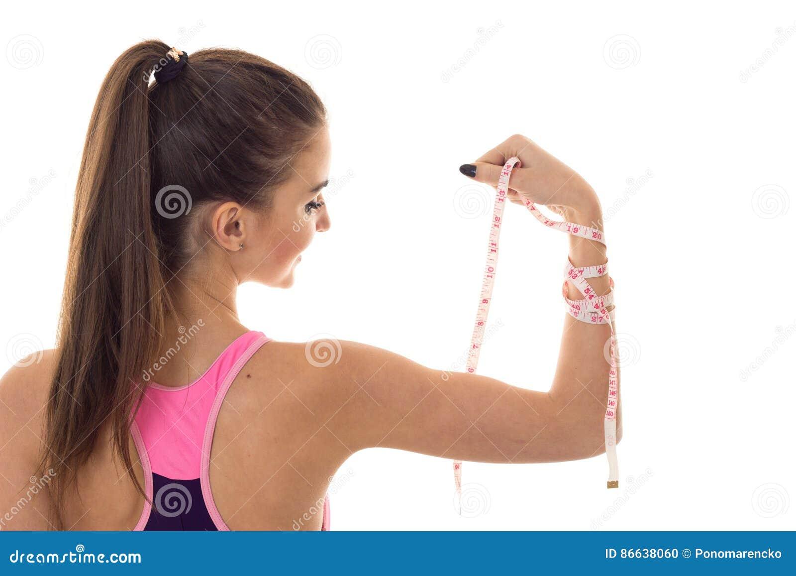 Una ragazza sta affrontante indietro e tiene a disposizione un primo piano di misurazione del nastro isolato su fondo bianco
